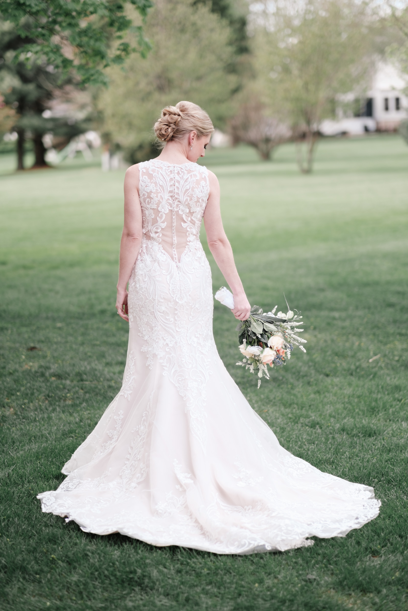 back of brides dress while she hold her flowers by her side and looks down at them