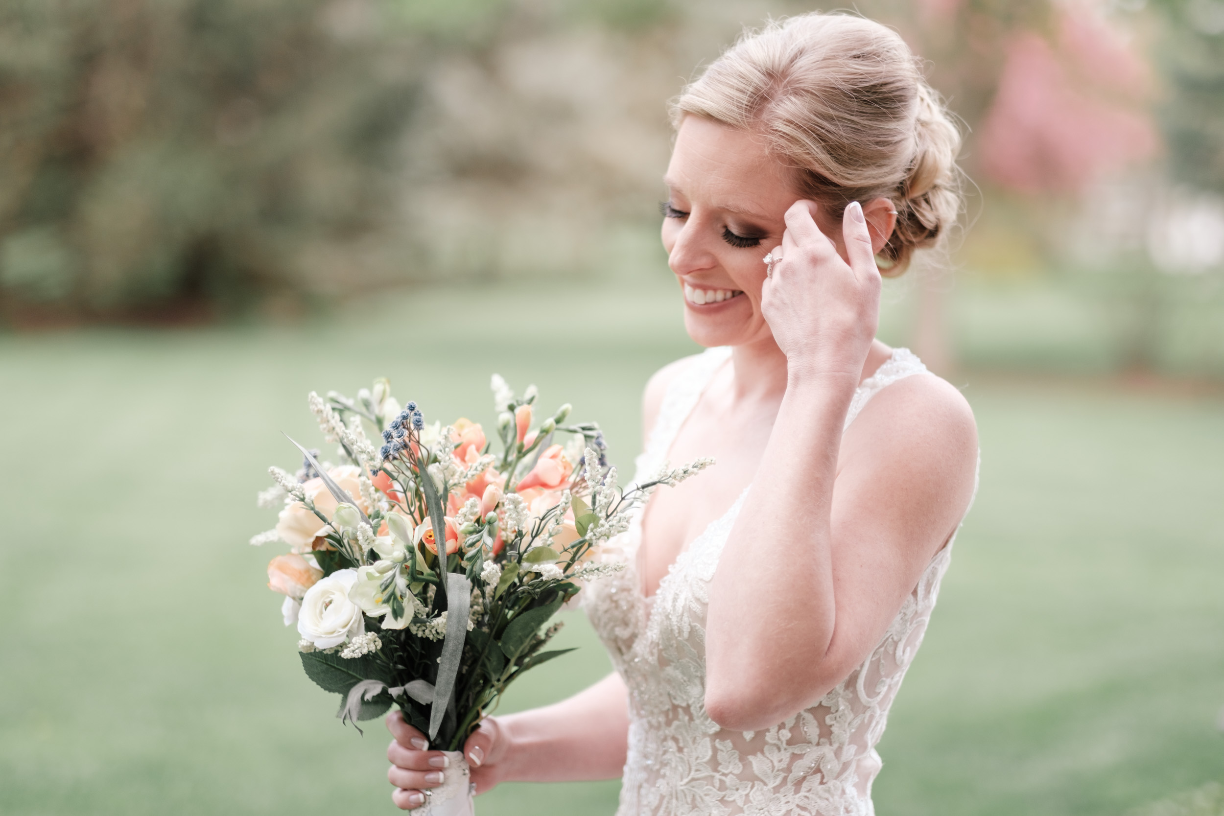 outdoor candid portrait of bride laughing and looking at wedding day flowers