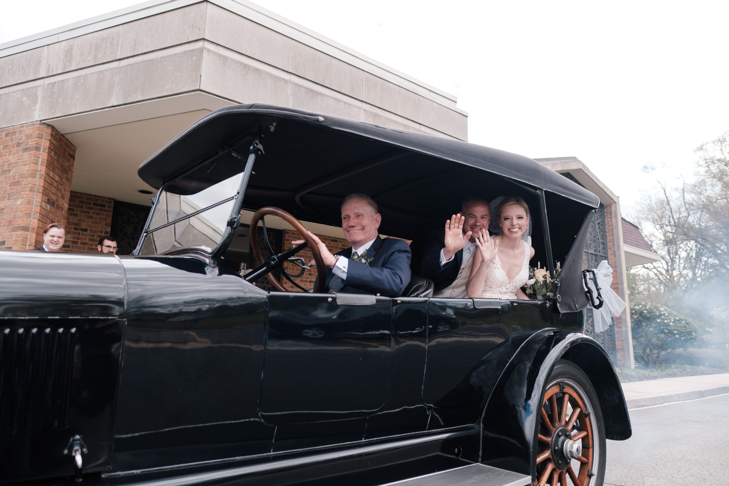 bride and groom ride away in classic car 1921 NASh convertible on wedding day