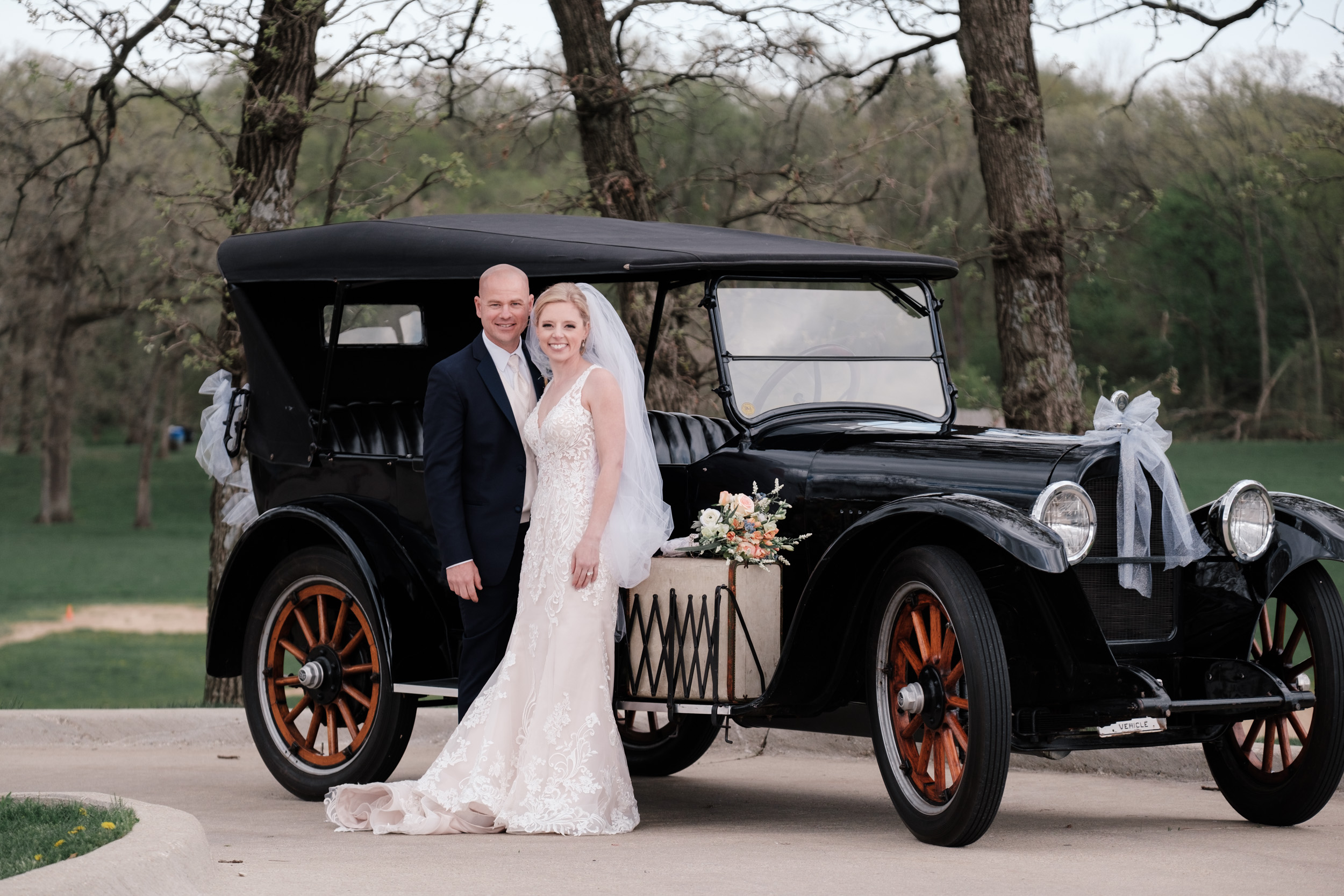 Bride and groom laugh in front of 1921 Nash at the brix