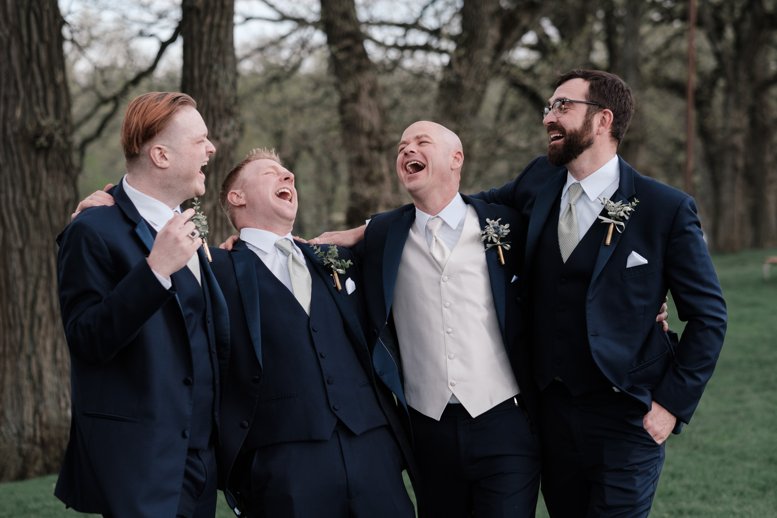 candid portrait of groom and groomsmen on wedding day laughing
