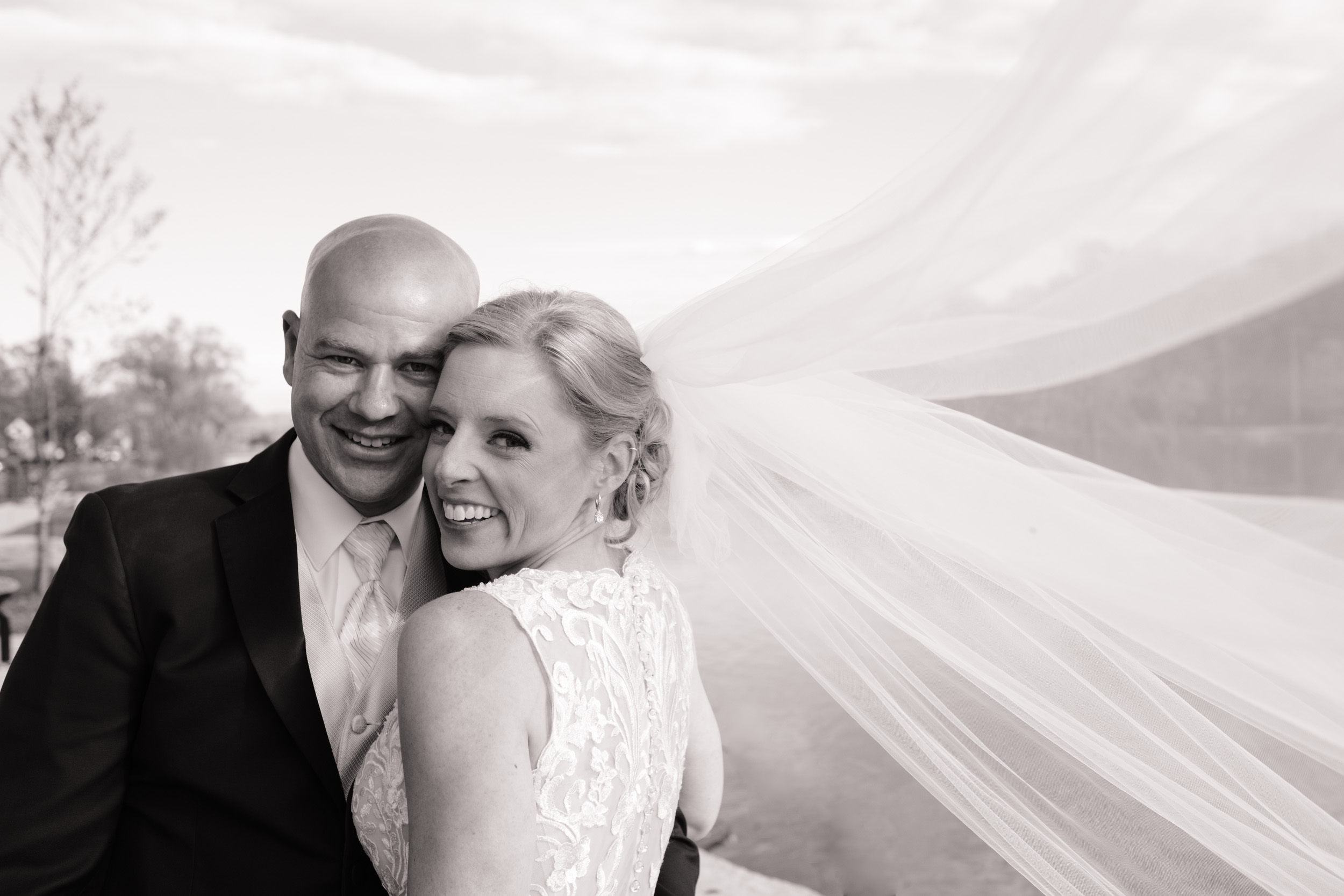 laughing portrait on wedding day with long veil blowing in the wind