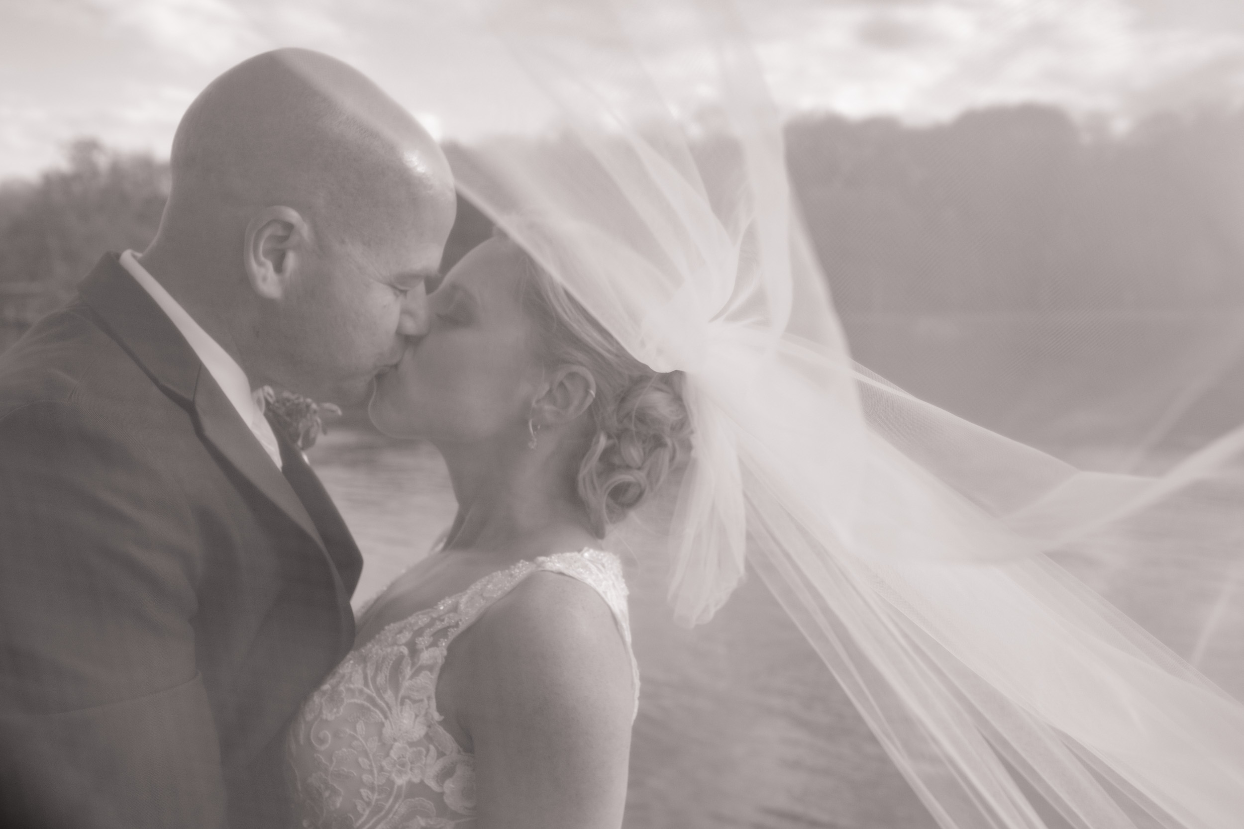 laughing portrait on wedding day with long veil blowing in the wind at the brix