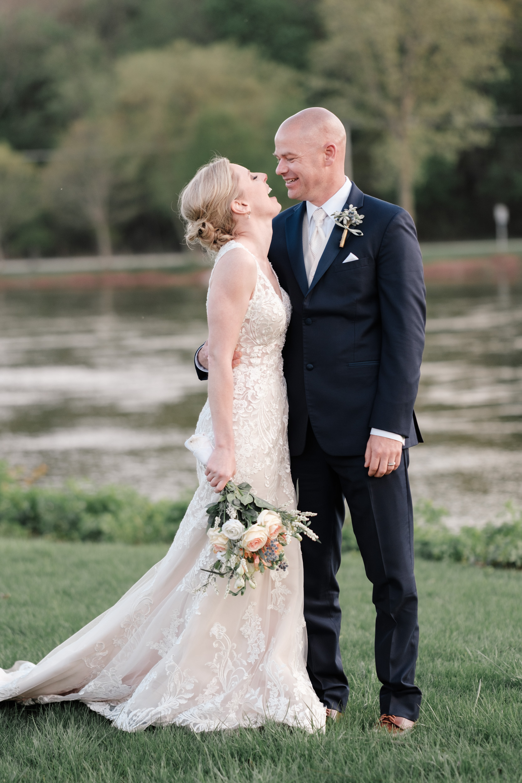 candid portrait of bride smiling at bride along river at the brix on their wedding day