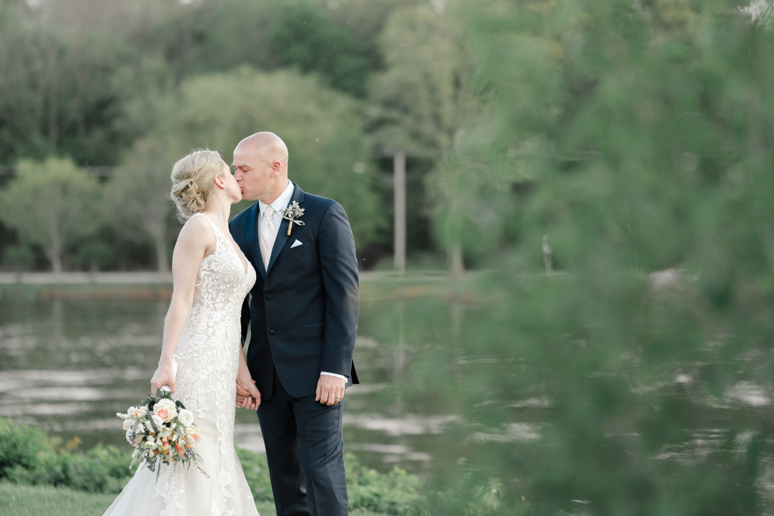 candid portrait of bride kissing at bride along river at the brix on their wedding day