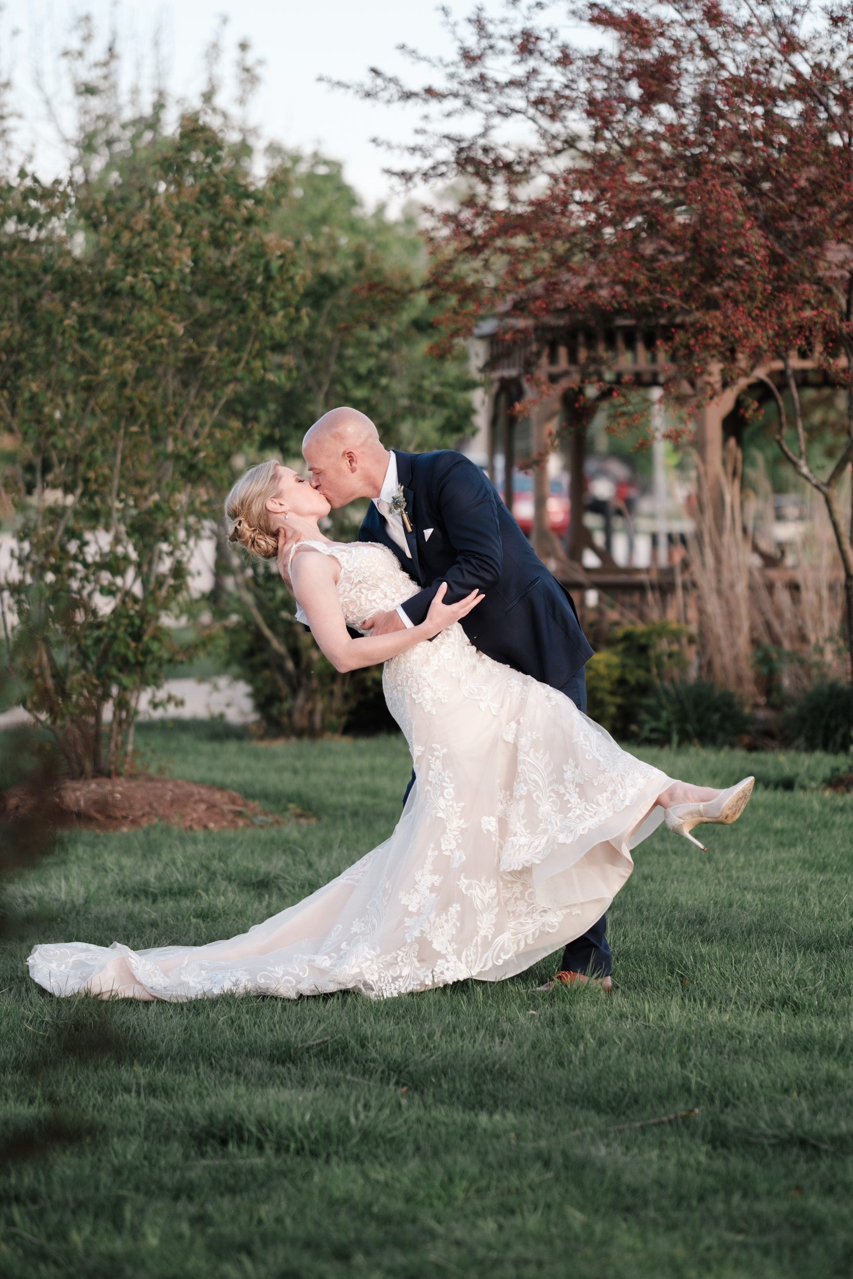 groom dipping bride for a kiss along the fox river at the brix candid natural and in love