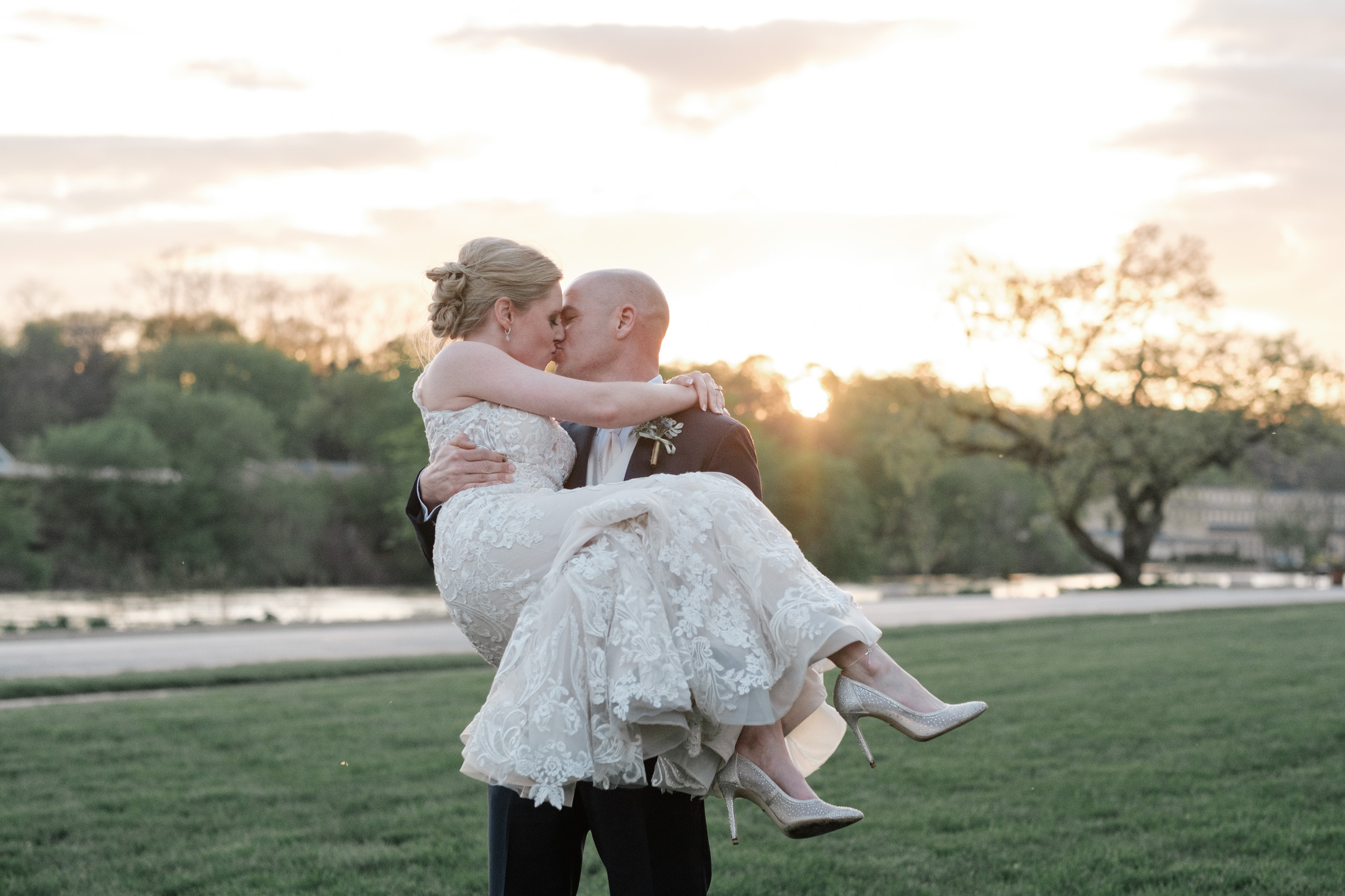 Bride and groom lovingly embrace at the brix at sunset