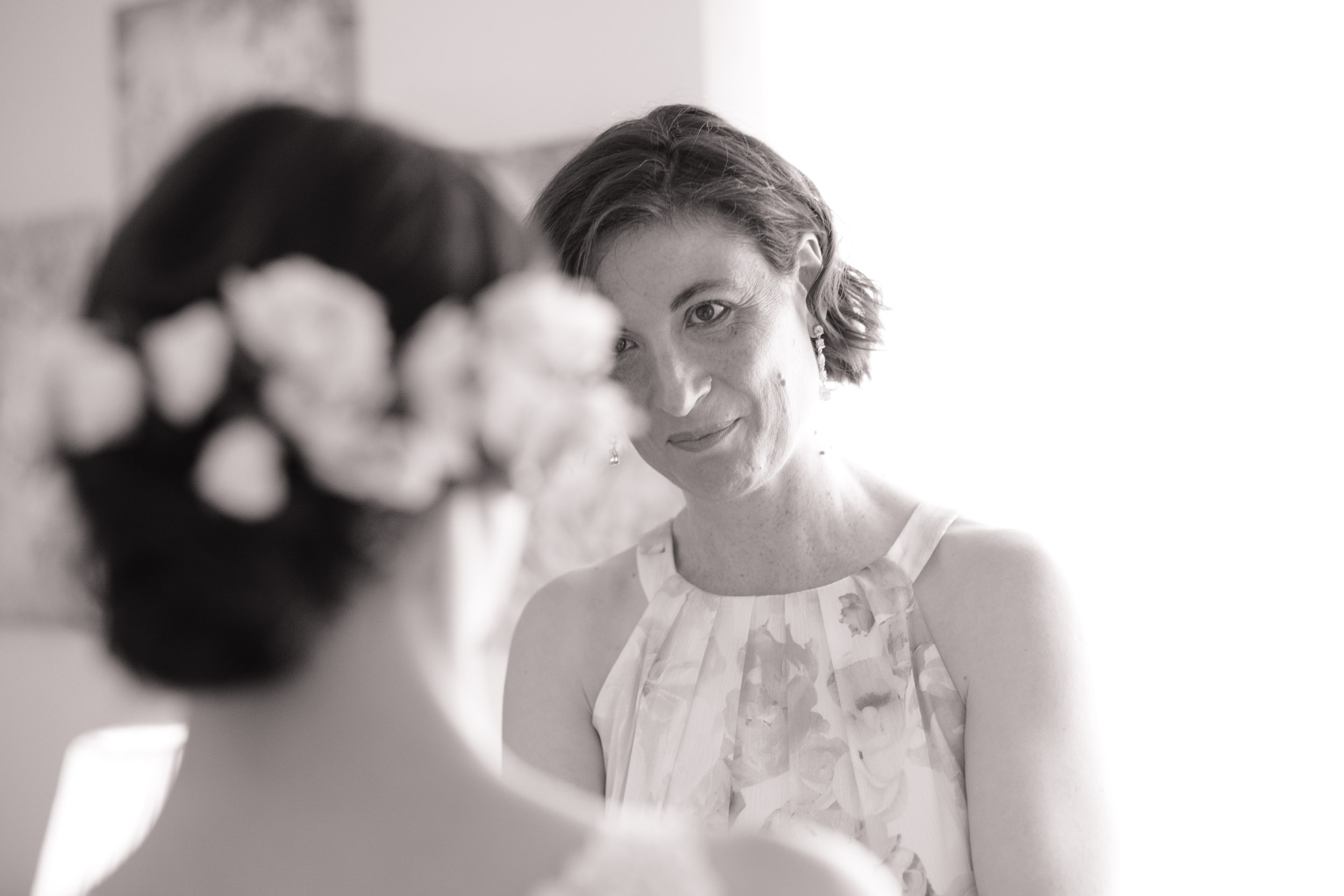 black and white mother of bride wiping tear away while holding daughters hands on her wedding day