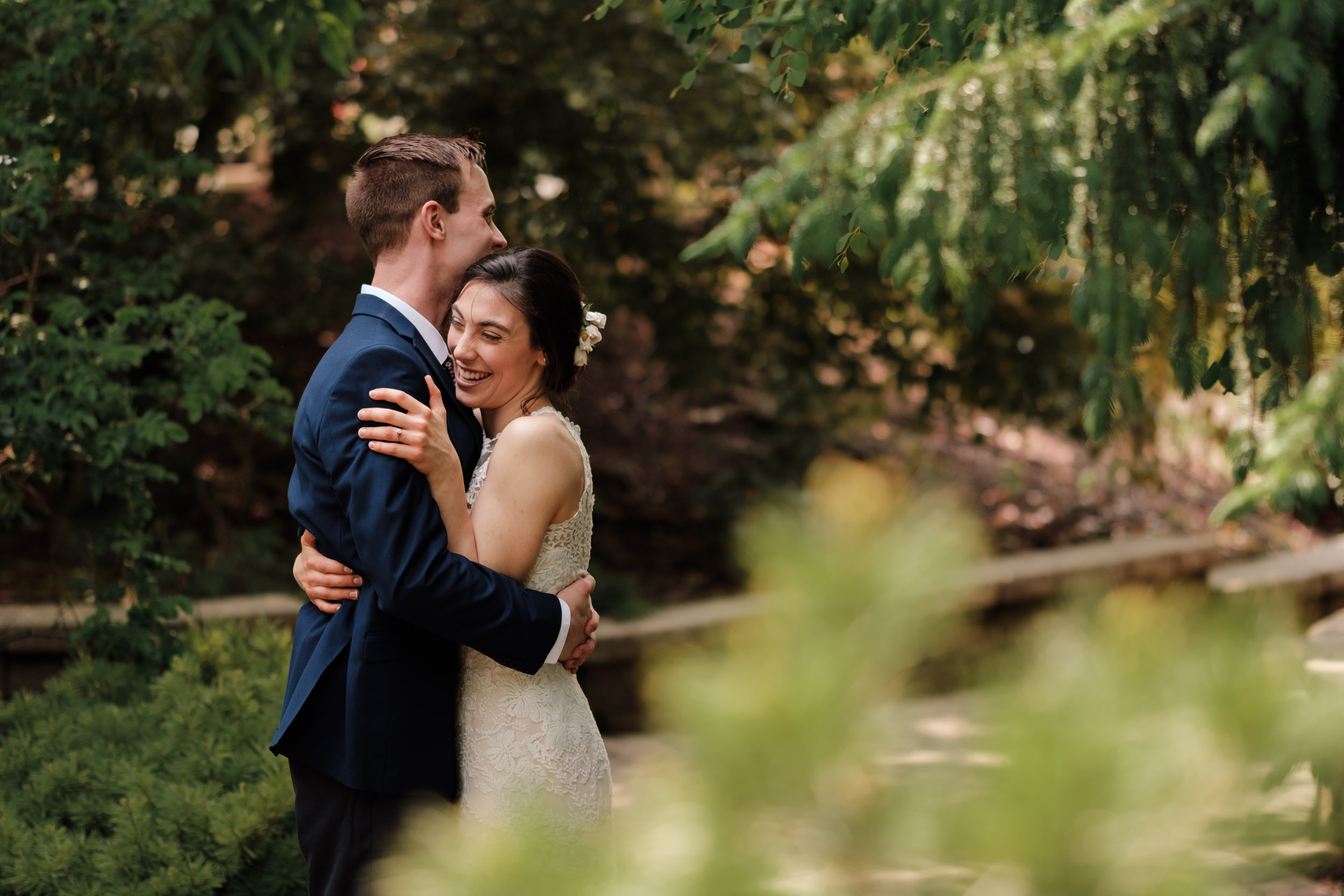 blue suite, eggshell lace bridal dress floral tie embrace on wedding day first look natural candid gardens of woodstock