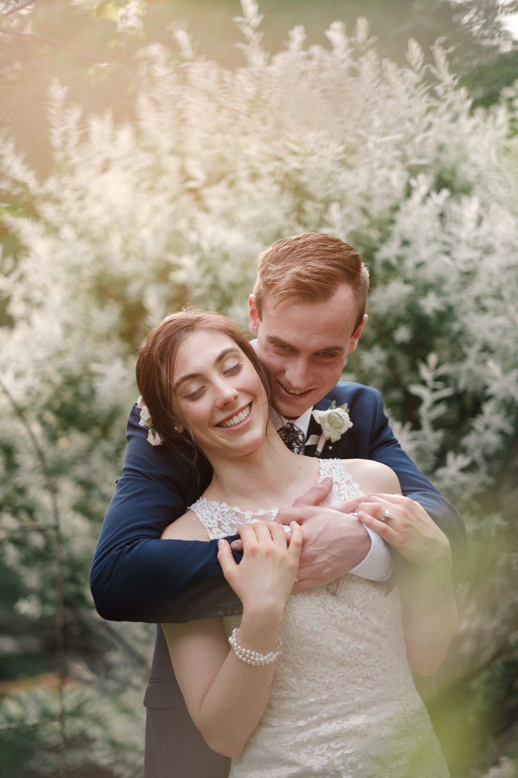 rockford wedding gardens of woodstock couple embrace and laugh blue suite flower crown