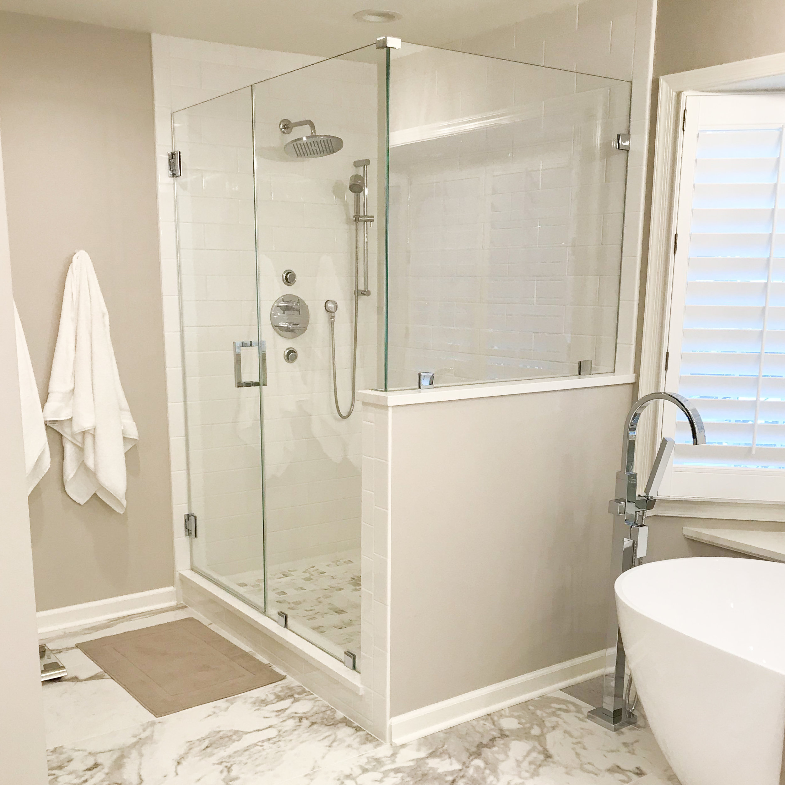 Sleek transitional bath uses a mix of warm and cool shades with a bit of shine from the crystal lighting and polished chrome accents to create a relaxing and serene space.