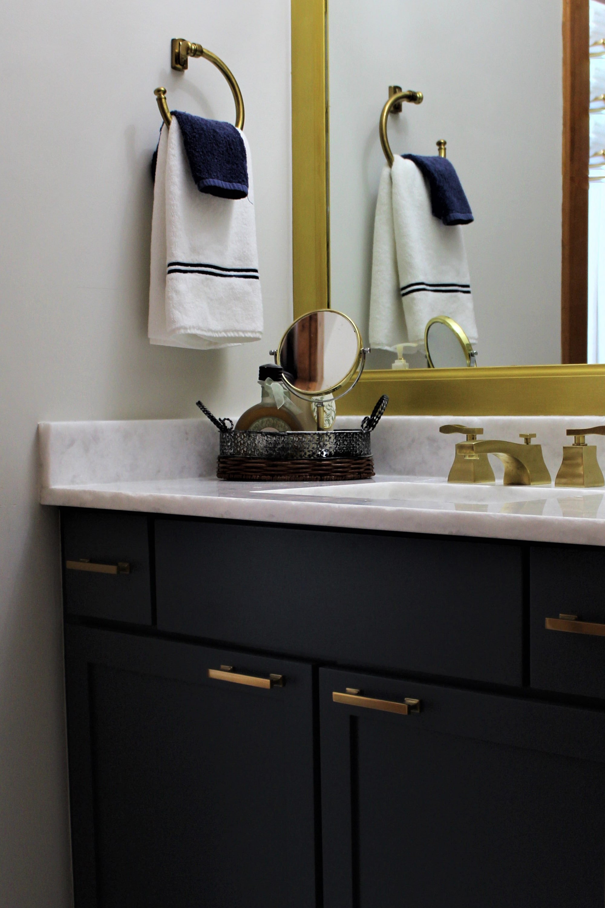 An updated Traditional look for this Jack and Jill bath is achieved with classic navy vanities that are highlighted by burnished brass accents and light gray cement tiles.