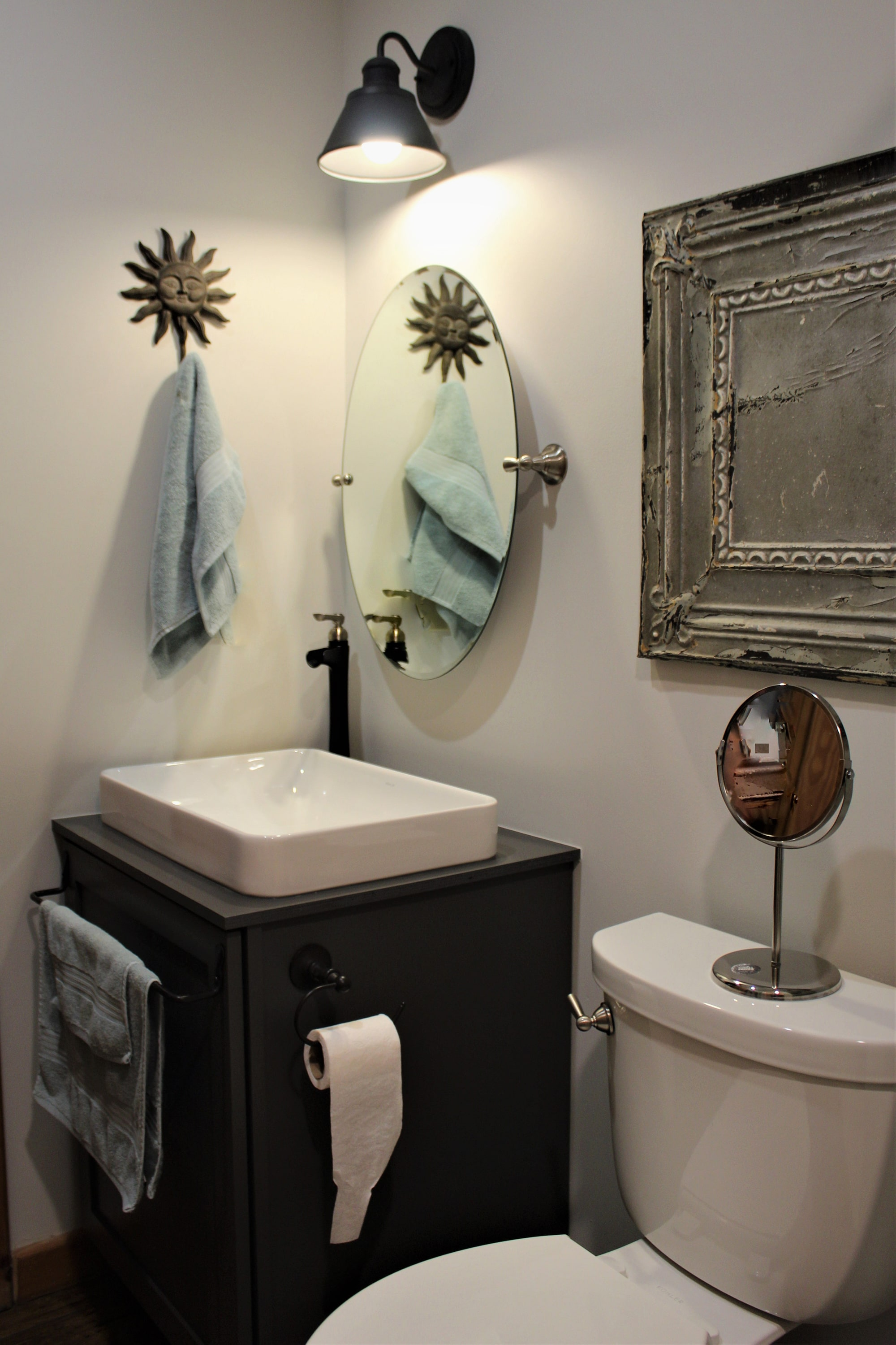 This Chic Industrial bathroom with charcoal gray cabinetry, a white vessel sink with black and satin nickel faucet, barn style lighting, and weathered accents work together to create a bath full of charm and warmth.
