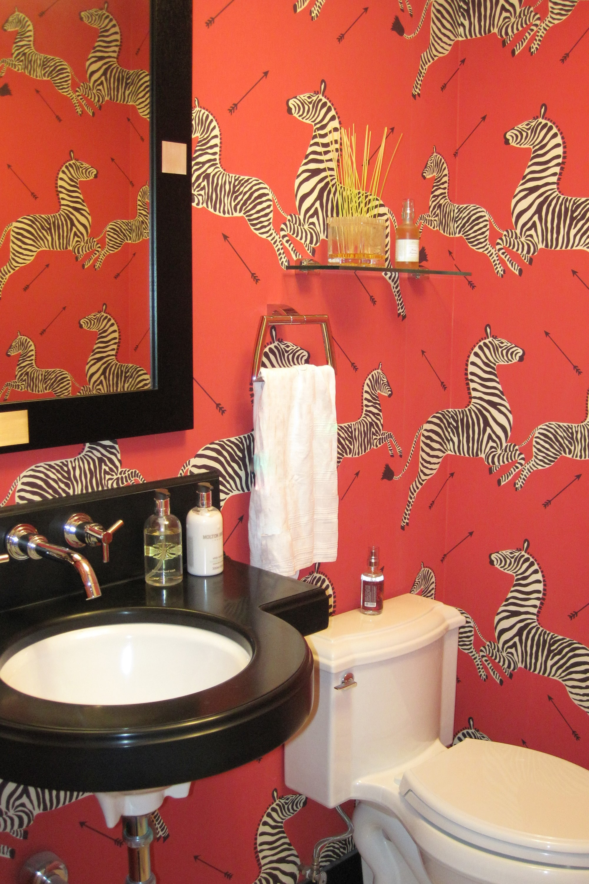 This powder room is a Modern Neo-Classic jewel box. The vibrant polished nickel accents, bold zebra wallpaper, and a custom floating vanity are elegant and whimsical.