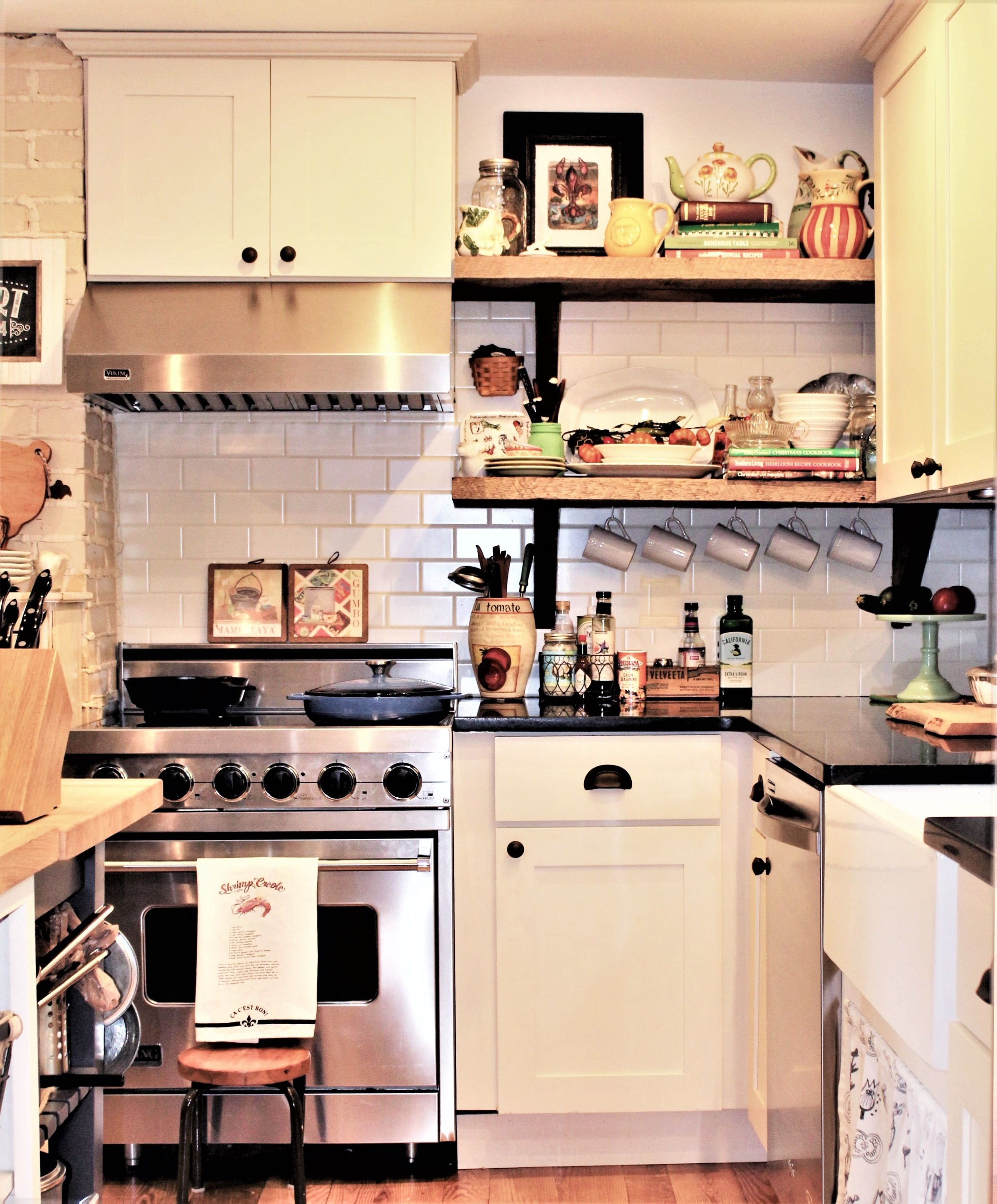 A historic cottage keeps its charm with the painted brick chimney, pine floors and warm white shaker cabinetry. The honed black countertops play off the birdcage light which is accented by a vintage piece of tin on the ceiling. The Eggplant color mobile butcher block cart add a bit of color and flexibility to this cottage kitchen but blends with the rest of the butcher block island when positioned at the end of the island.
