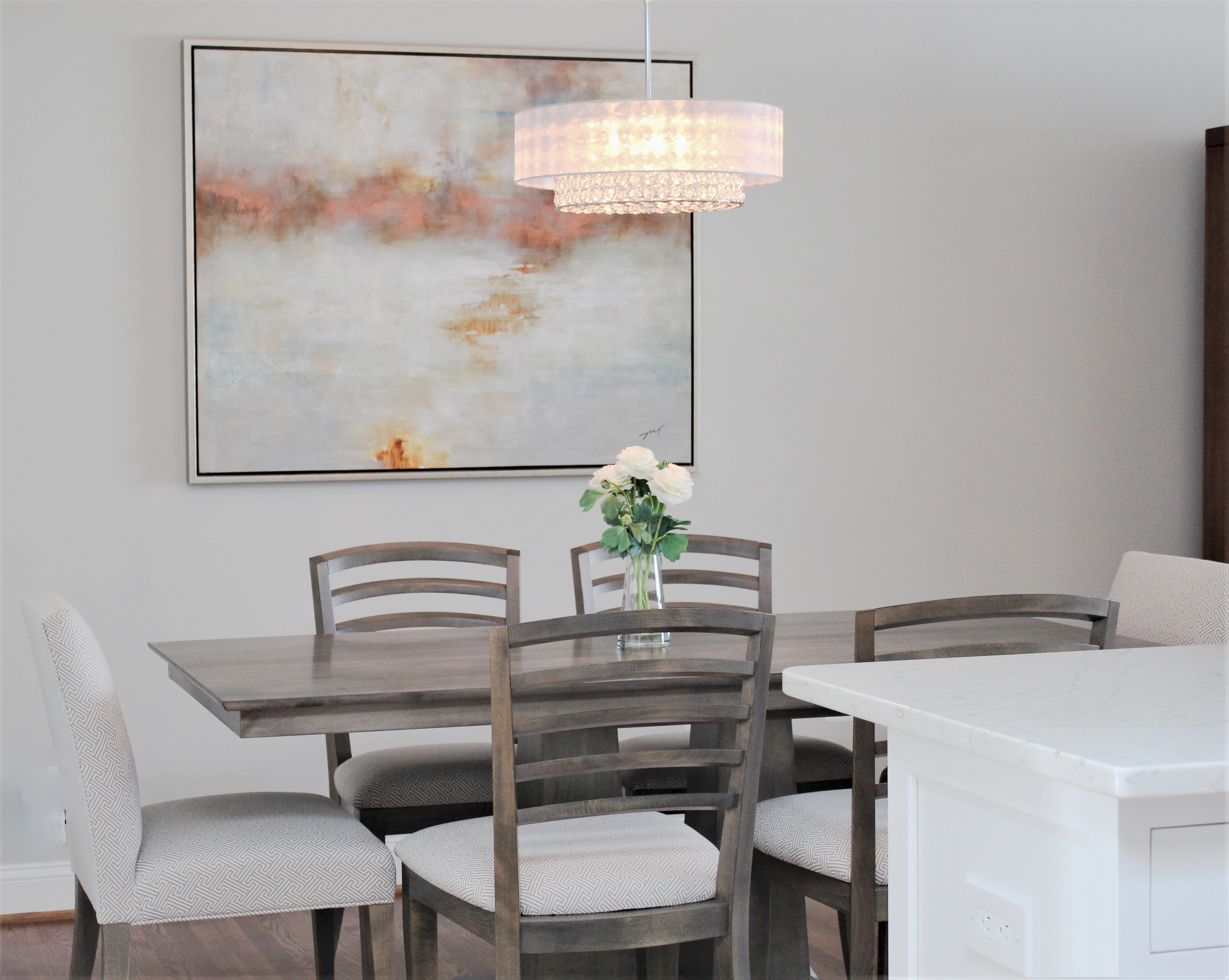 An open concept kitchen was created by removing the dining wall. Shades of white and taupe are carried thought out the space showing up in the glass tile backsplash, dining light & furniture. Simple recessed lights and white quartz counters keep the space clean and bright which accent the glimmer of the stainless appliances, backsplash and dining light.