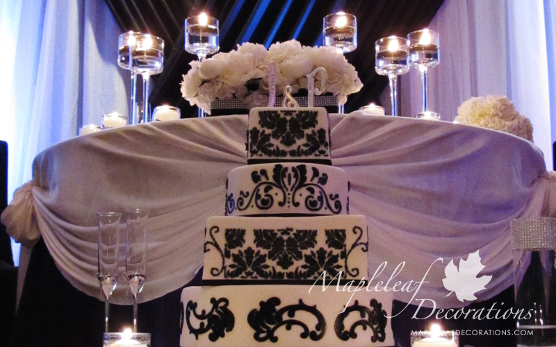 toronto-wedding-hall-decorations-backdrop-and-head-table-decor-la-primavera-banquet-hall-cafe-style-sweetheart-table-black-and-white-ivory-satin-peonies-centrepieces-candles-bling-accessories-montecassino-glass-vases-silver-mesh-cake-table-damask.jpg