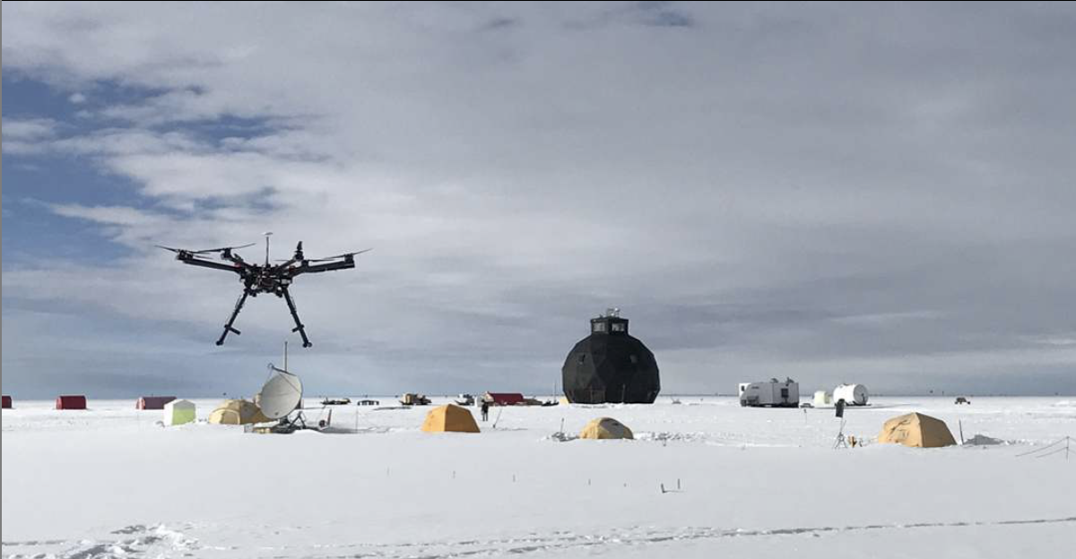 East Greenland Ice-Core Project camp in 2018. The three-story black dome in the distance, a multi-rotor drone in the foreground used to prototype a way of collecting air samples aloft. Photo credit:    Egripcamp Instagram   .