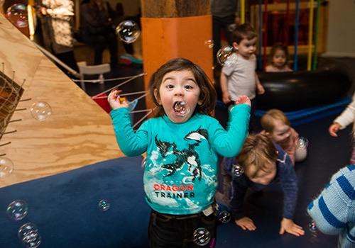 girl with bubbles at recess dumbo interior brooklyn new york city ny
