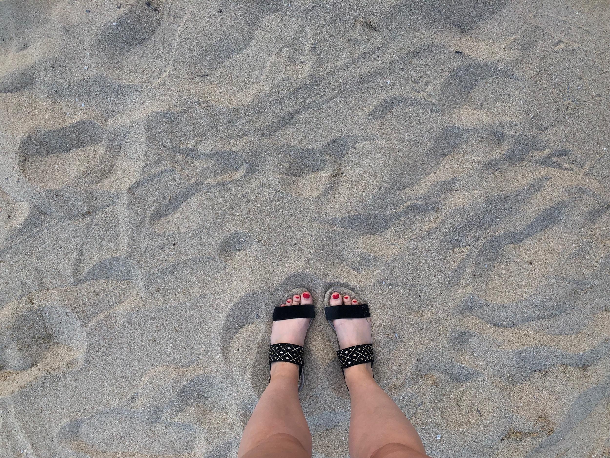 Vita, slitna och lite skitiga bil-fötter på strandpromenad i Cala Major.