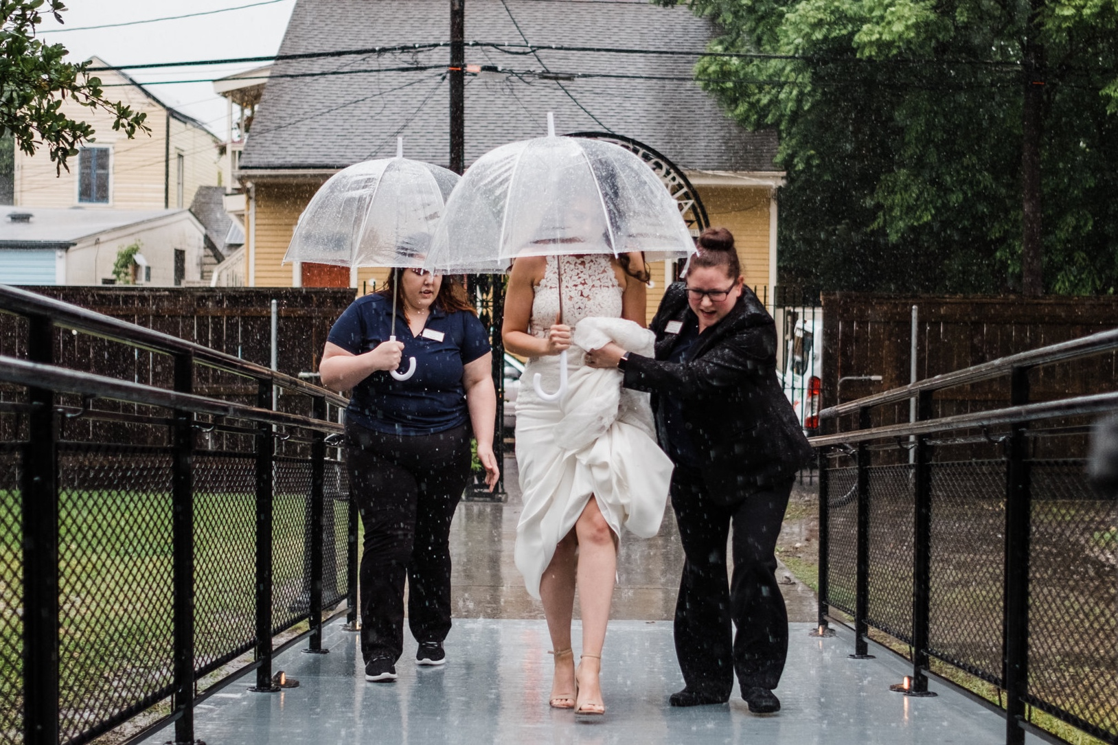 Amanda helps her bride Ashli keep dry as they head into the ceremony.   Credit: Dark Roux Photography