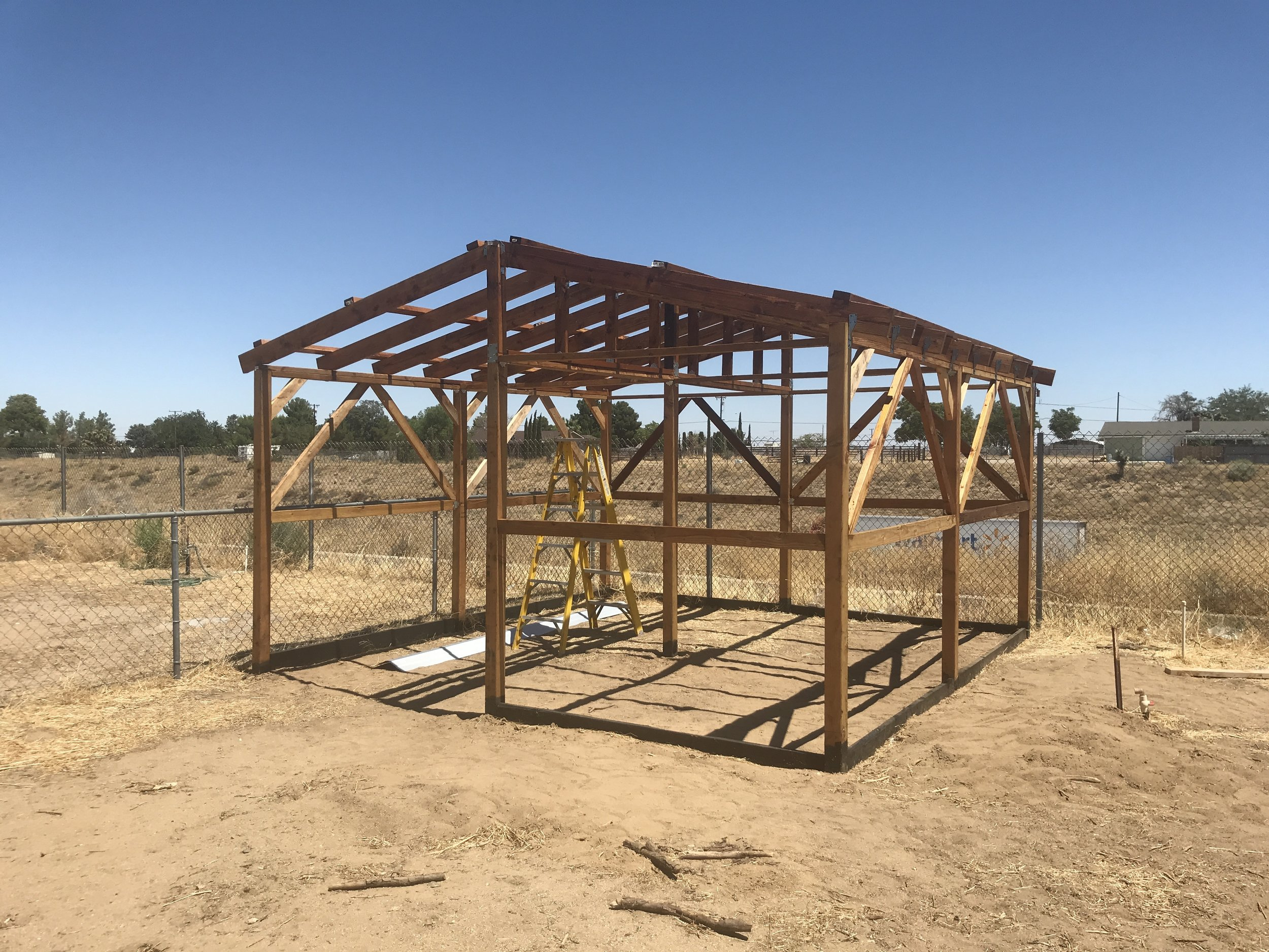 Treated the wood, added cross bars for support and 2x4's on top for attaching metal roofing.