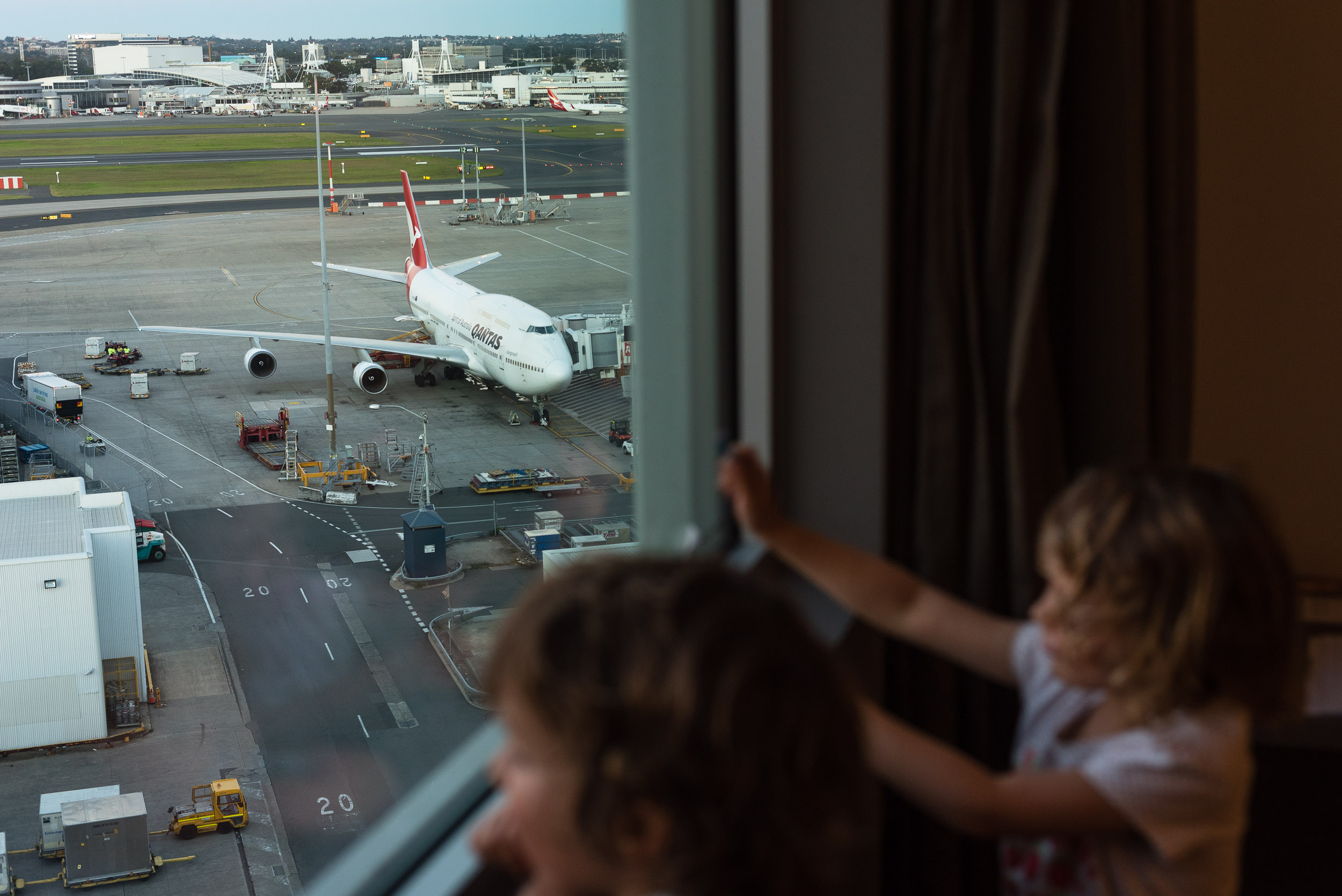 Finn and Holly looking at planes taking off, at Sydney airport, from room 802, level 8 of Rydges Hotel, Sydney, Australia. We stayed the night before our flight out and the kids loved it!