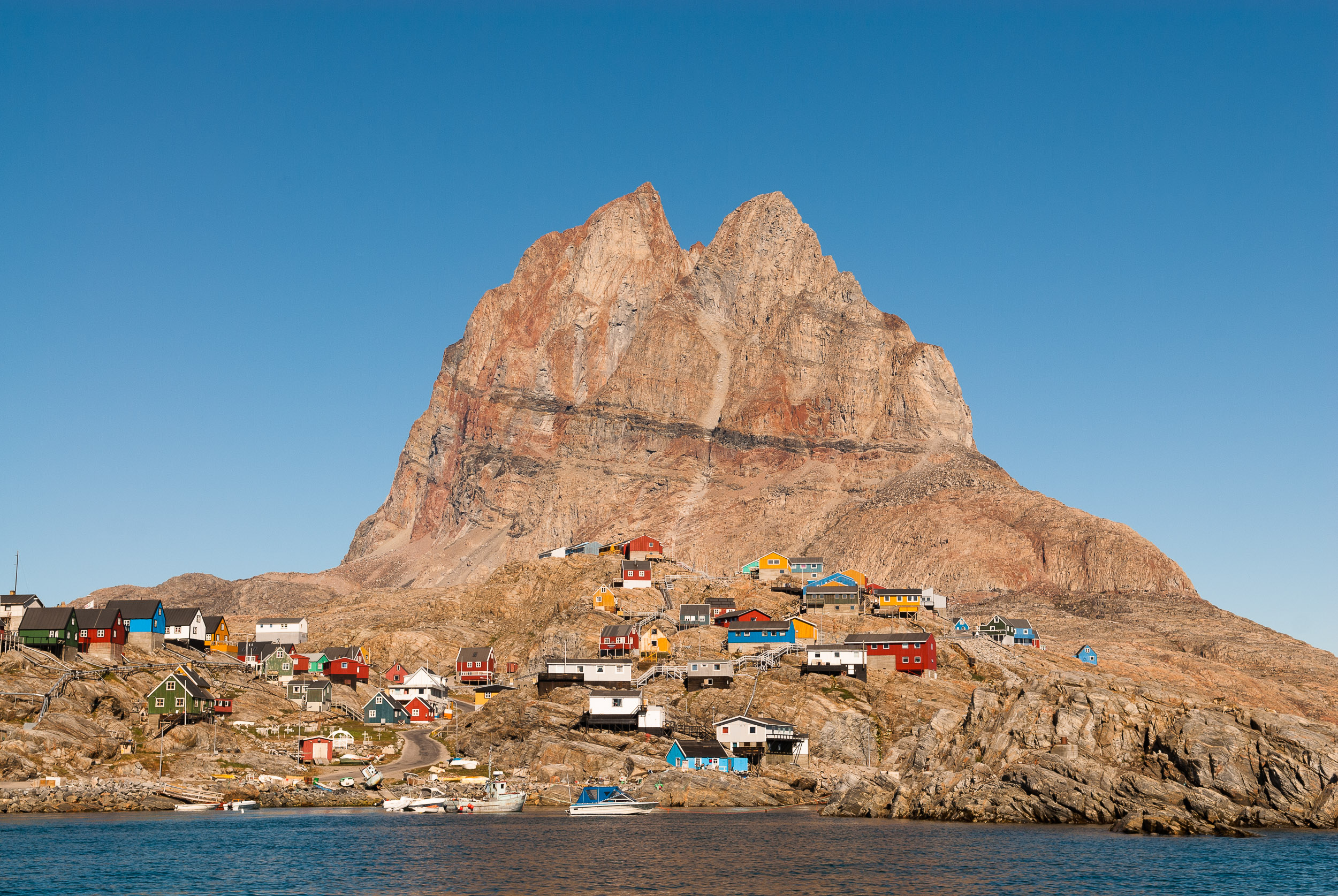 Summer time view of Uummannaq town and Uummannaq Mountain, Greenland. Uummannaq is has Greenland's most northerly ferry terminal and is a base for hunters and fishermen. During winter when the sea ice freezes over, Uummannaq hosts the World Ice Golf Championships.