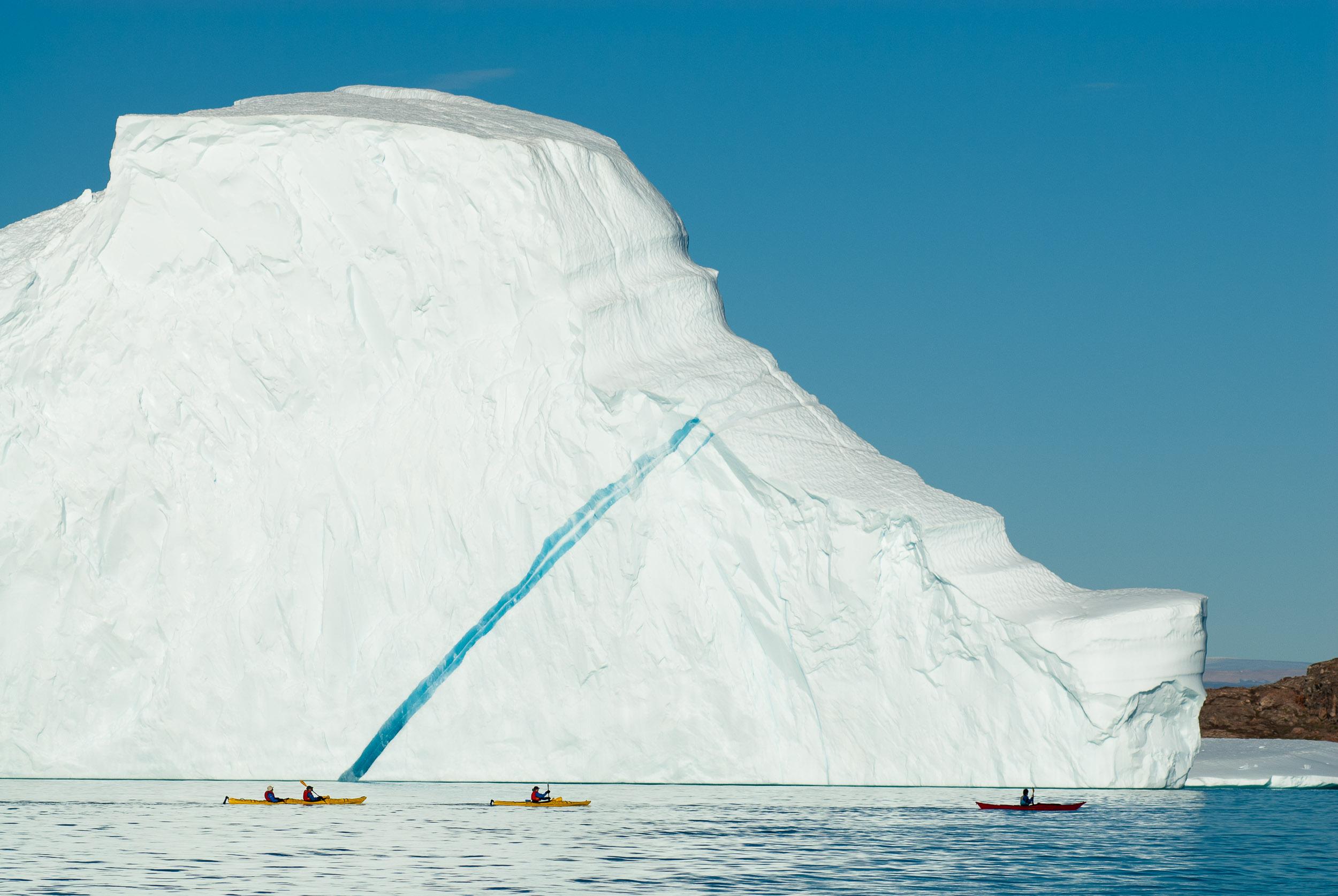 Tourists sea kayaking past an iceberg, Hall Bredning, Renland, Greenland.