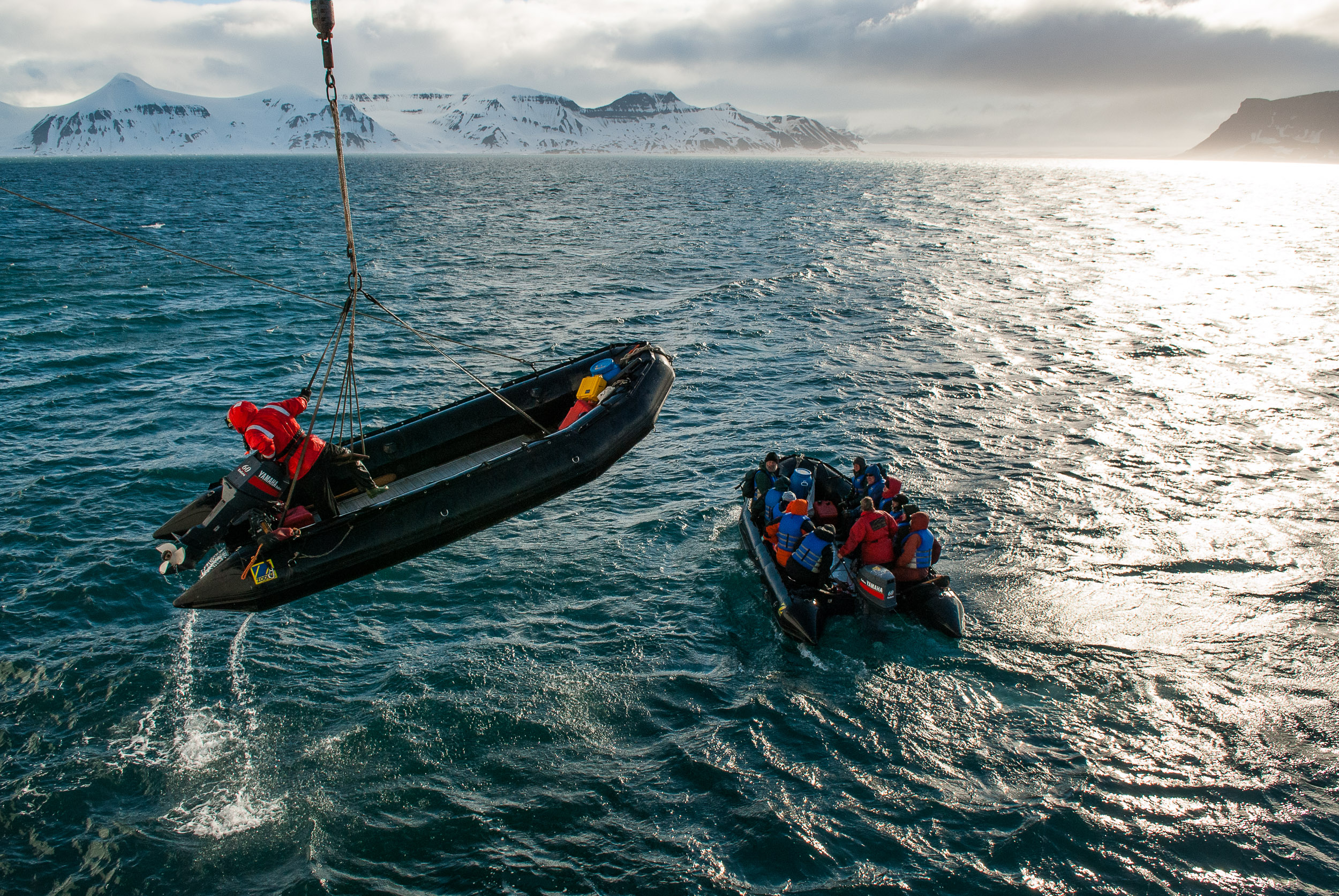 A polar guide and his inflatable motorized boat, known as a zodiac, being lifted onto the deck of the expedition cruise ship the  Akademik Sergey Vavilov,  Hambergbukta, Torell Land, Spitsbergen/Svalbard.