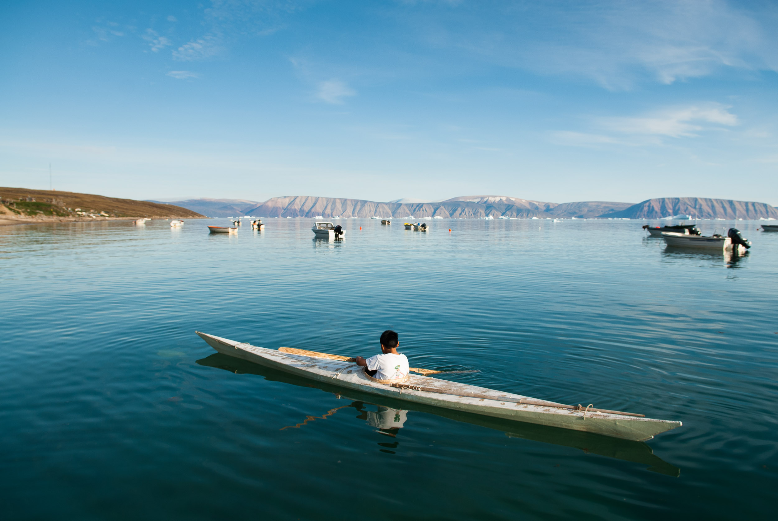 Inuit boy paddling a traditional sea kayak, Qaanaaq, Thule, Greenland.