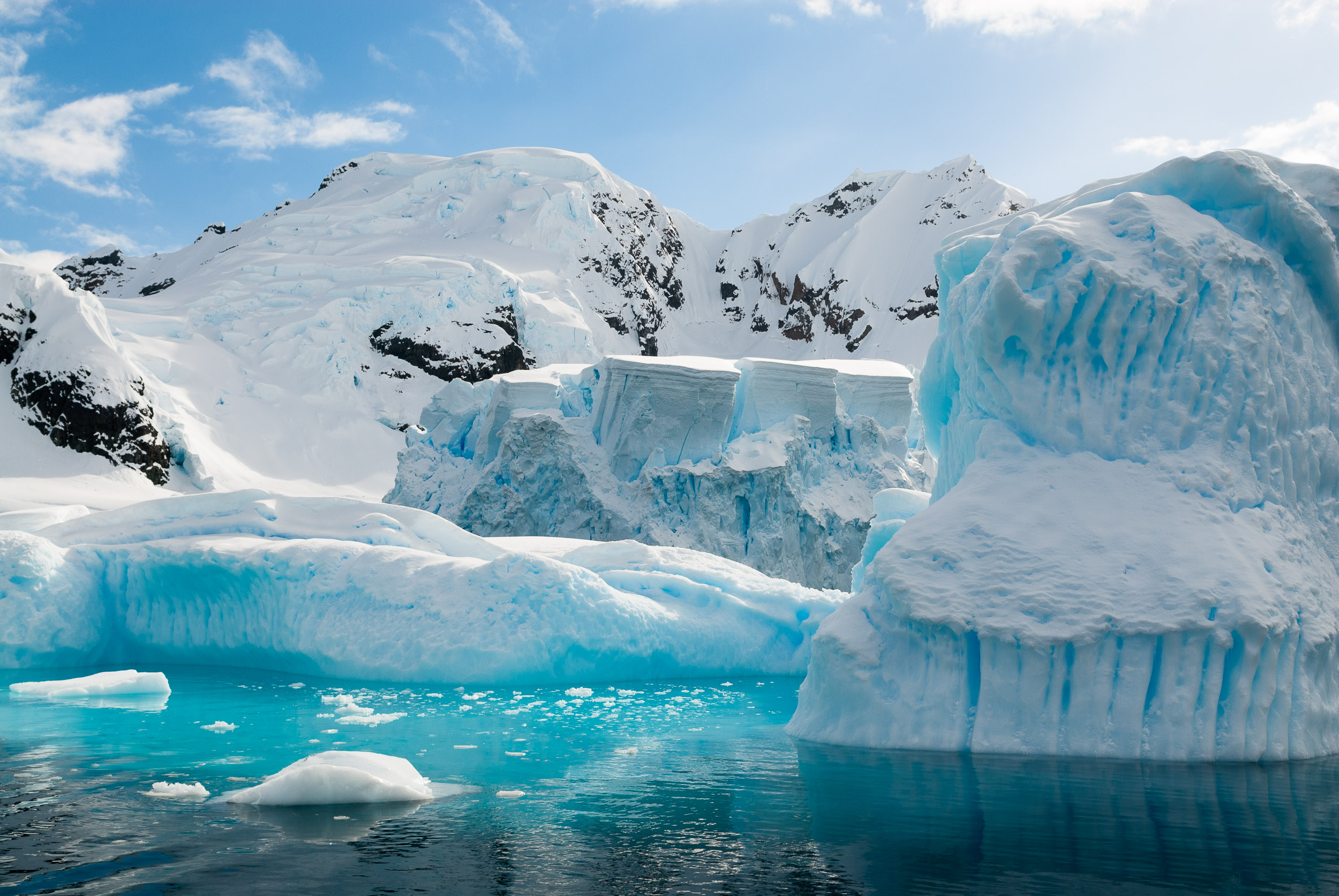 Glacier and icebergs, Paradise Harbour, Danco Coast, Graham Land, Antarctica. Due to its picturesque landscape, with dramatic mountains and glaciers, Paradise Harbour is visited by numerous expedition cruise ships each Antarctic summer.
