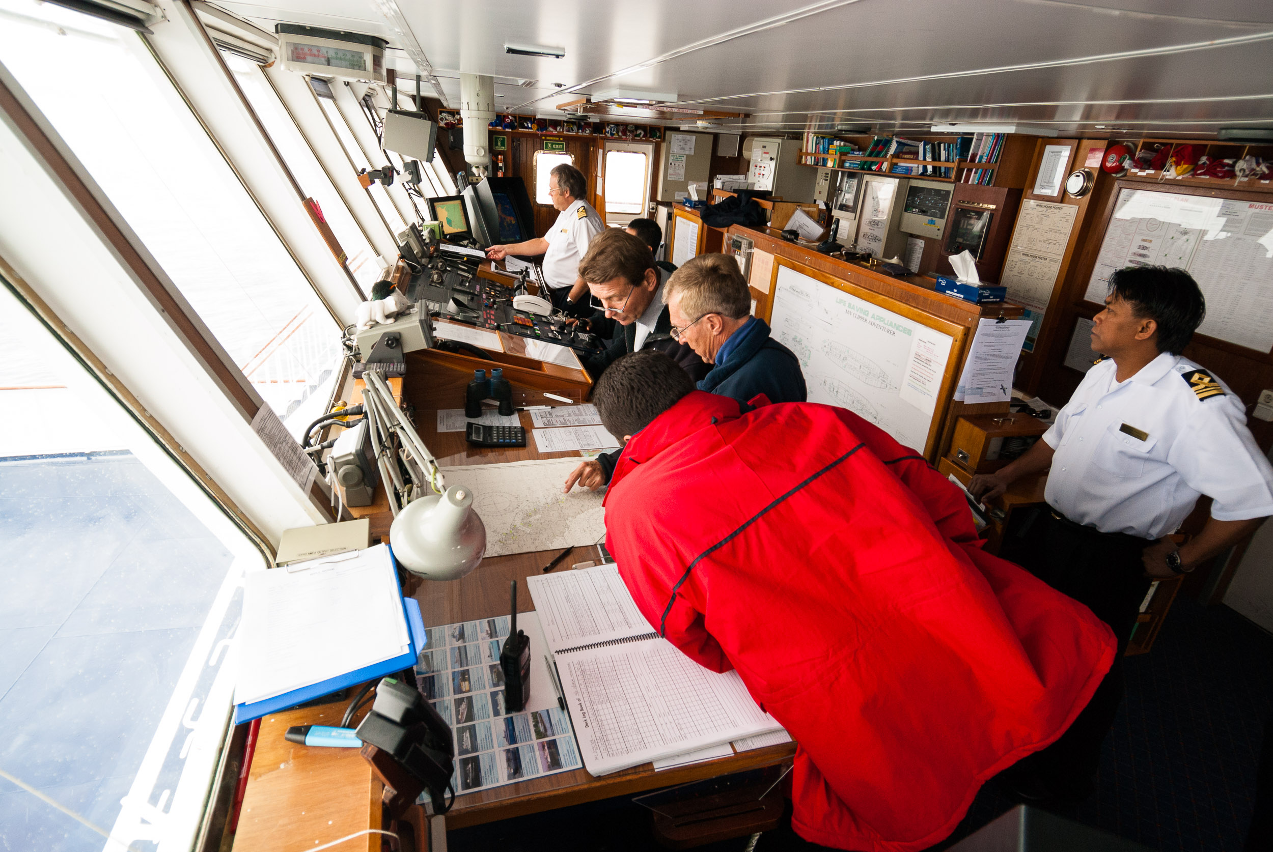 Expedition Leader, Laurie Dexter (blue jacket centre) discusses strategy with the Captain and First Officer on the bridge of the  Clipper Adventurer,  Moltke Harbour, South Georgia.