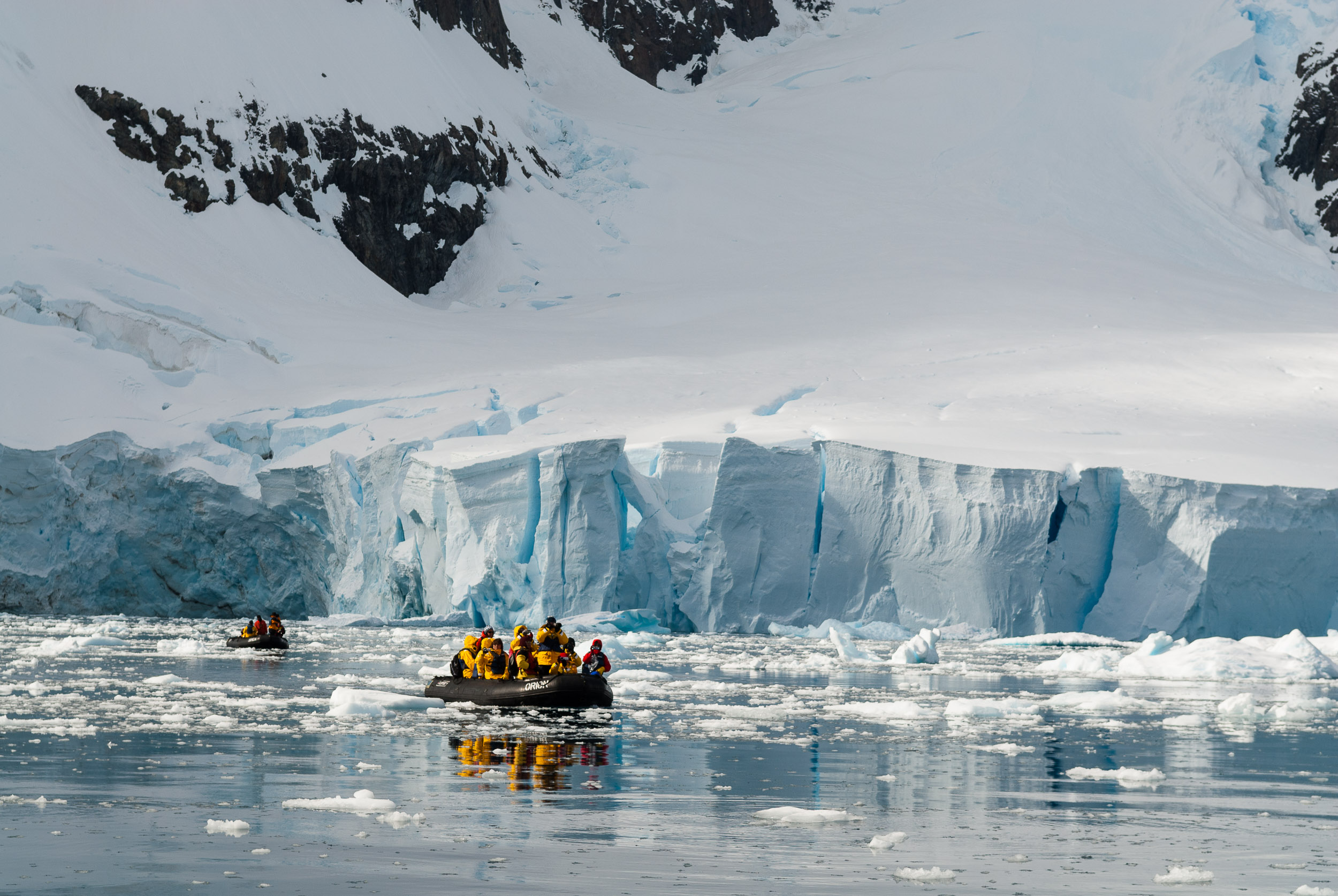 Tourists cruising through pack ice on motorised inflatable rafts known as zodiacs, Paradise Harbour, Danco Coast, Graham Land, Antarctica. Due to its picturesque landscape, with dramatic mountains and glaciers, Paradise Harbour is visited by numerous expedition cruise ships each Antarctic summer.