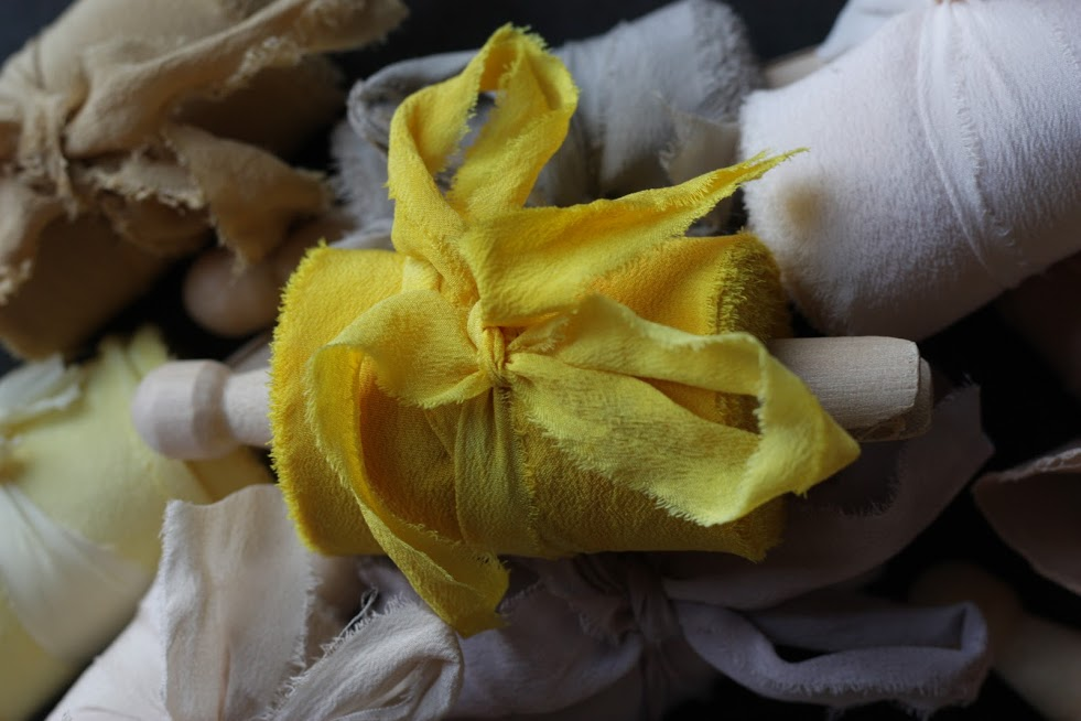 Turmeric dyed silk ribbon among other naturally dyed silk ribbons