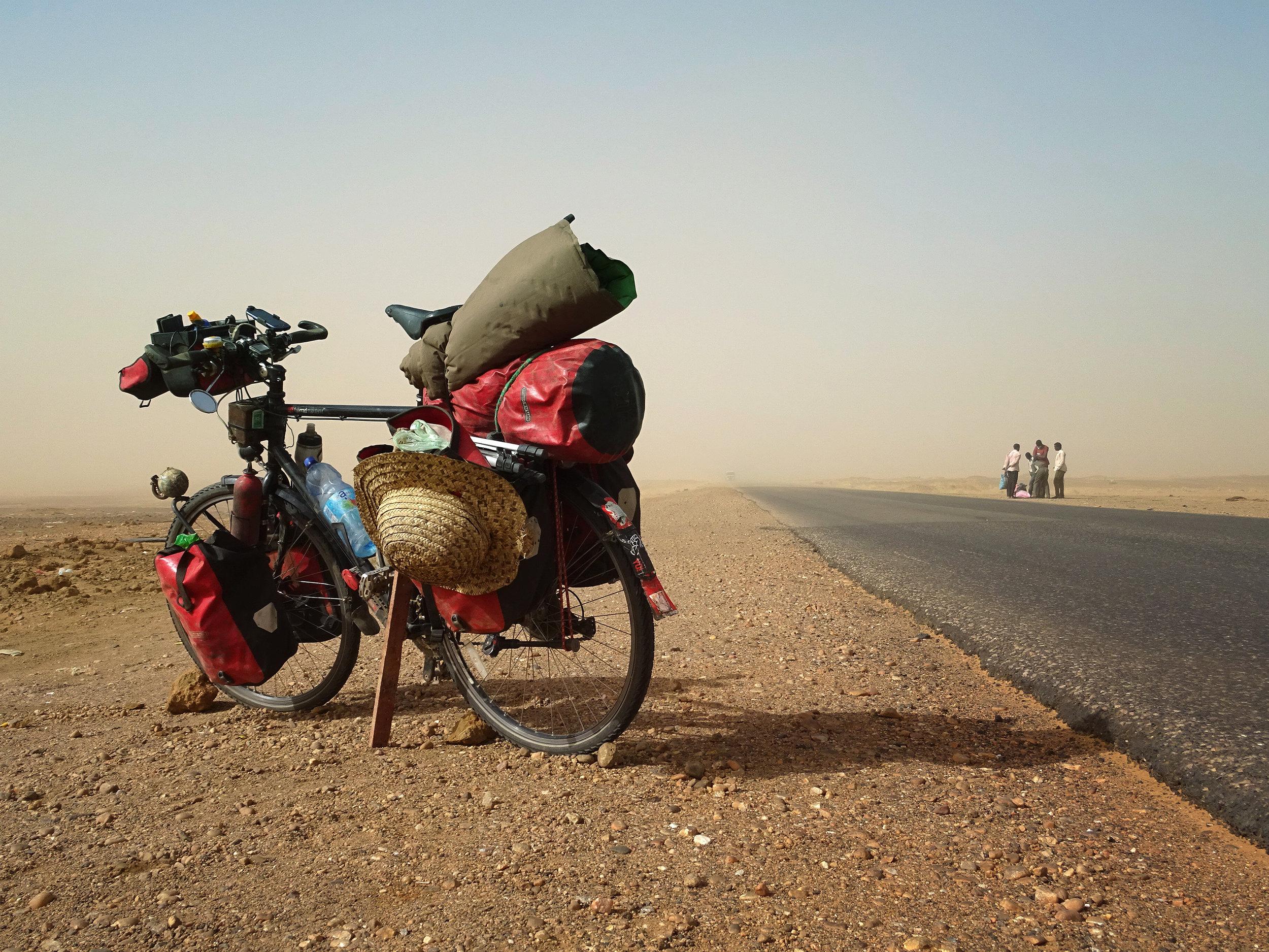 Ein Sandstrum fegt über den heißen Aspalt der Sudanesischen Sahara.jpg
