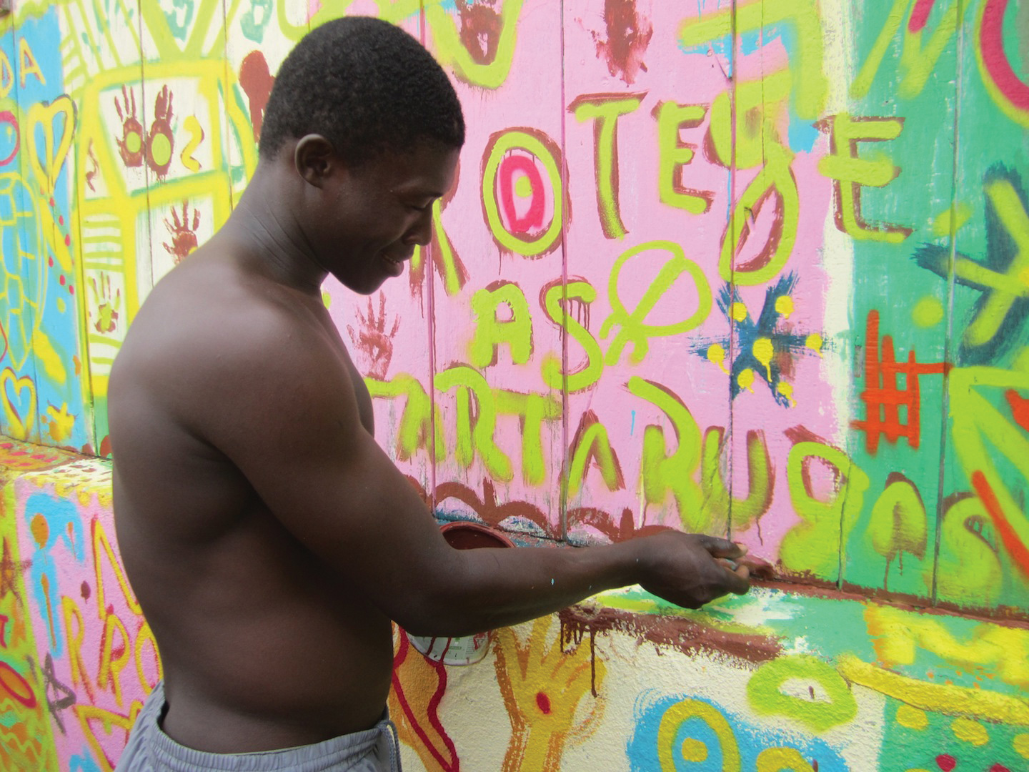 A member of the coastal community Morro Peixe helps paint an educational mural. © VICTOR JIMÉNEZ