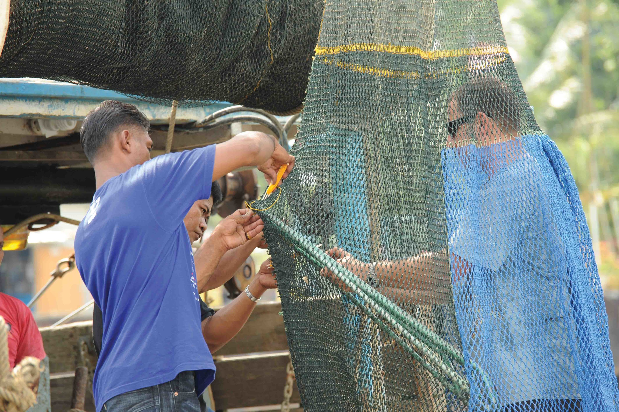 Staff members from the Marine Research Foundation in (Malaysia) work with local fishers to install TEDs in their trawl nets. © Nicholas J. Pilcher