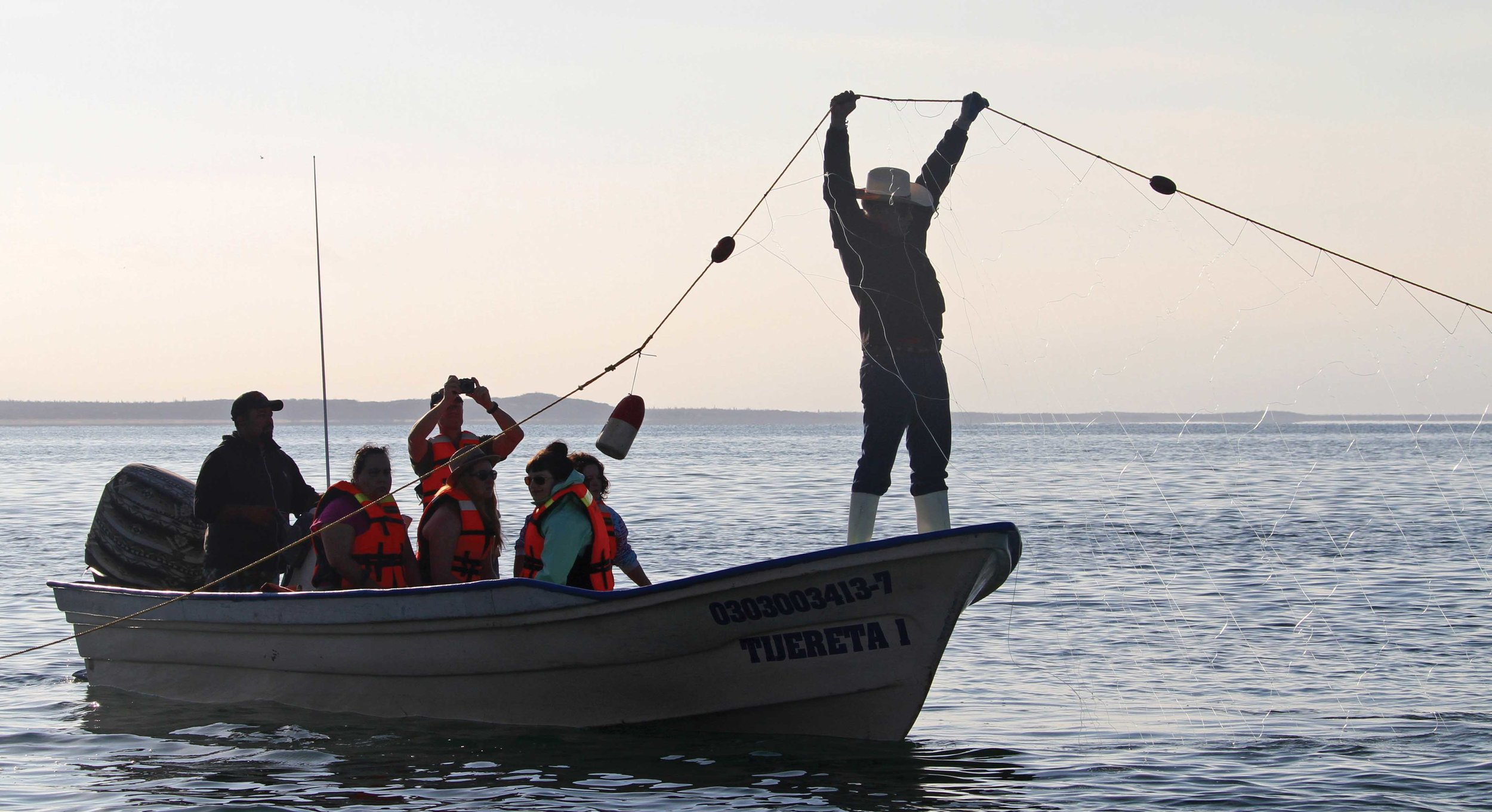 Tourists watch in Baja California, Mexico, as a fisherman conducts in-water sea turtle monitoring. © Karen Delaney Wolverton