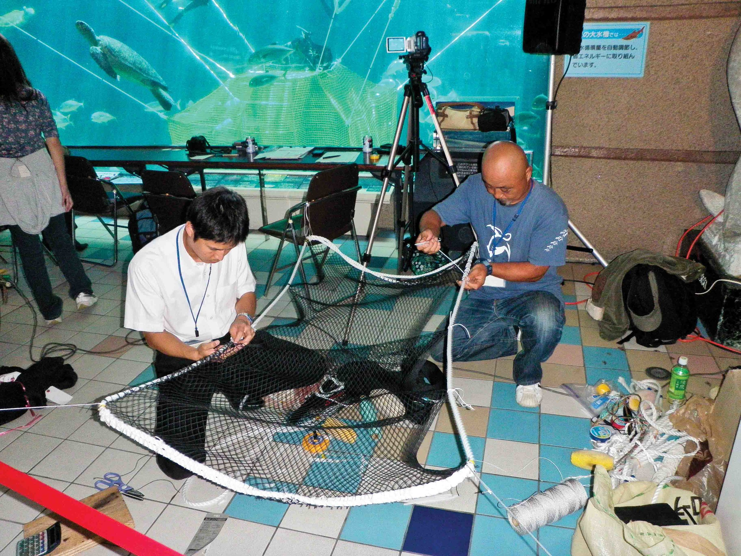 Workshop participants collaborate to modify the prototype for a pound net escape device (PED) as part of experimental trials in Kobe, Japan. © Sea Turtle Association of Japan