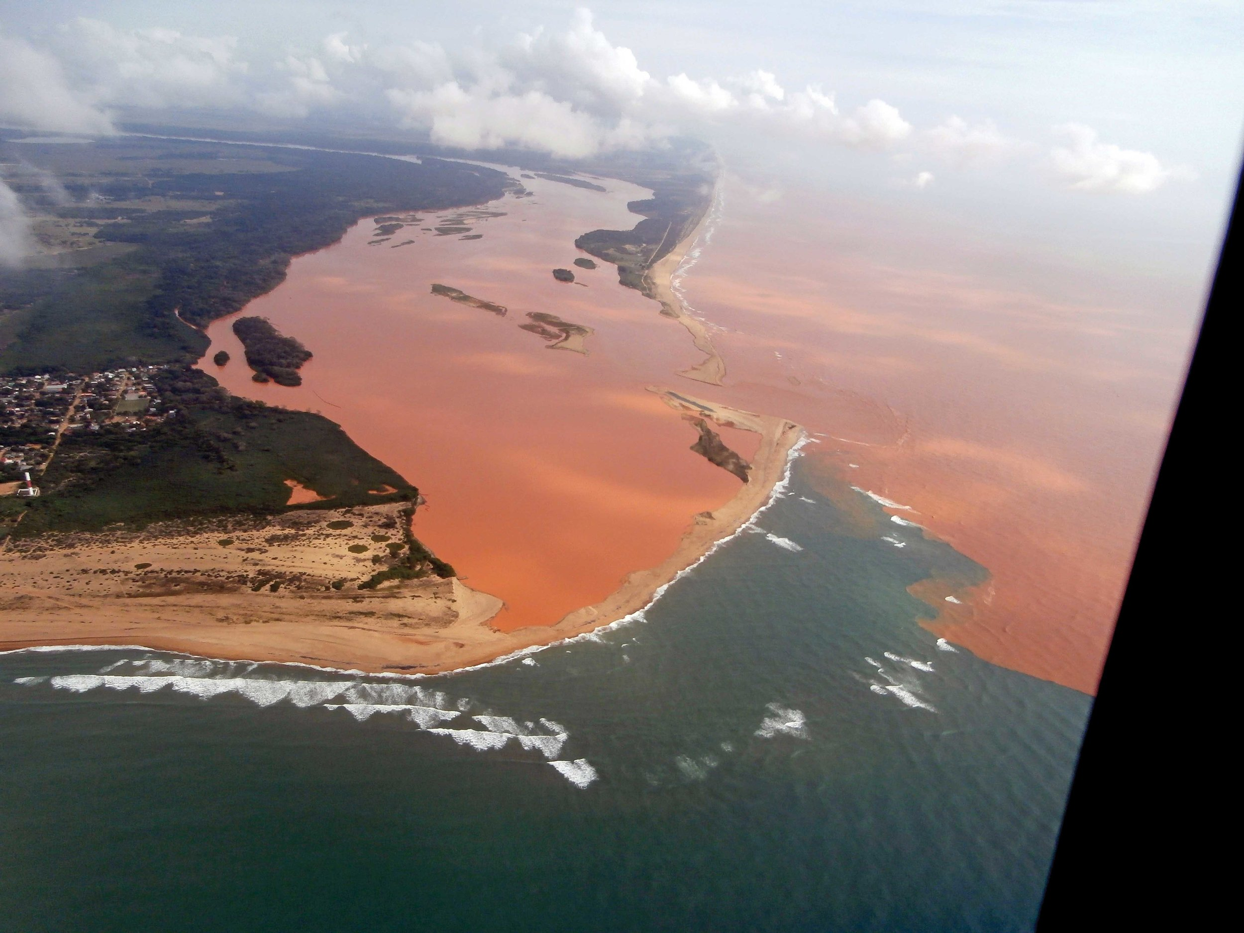 An aerial photograph of the mouth of Brazil's Rio Doce shows the distant impact of a tailings dam failure 650 kilometers (404 miles) upstream. The beach is home to globally important leatherback and loggerhead nesting populations. © CENTRO TAMAR-ICMBIO