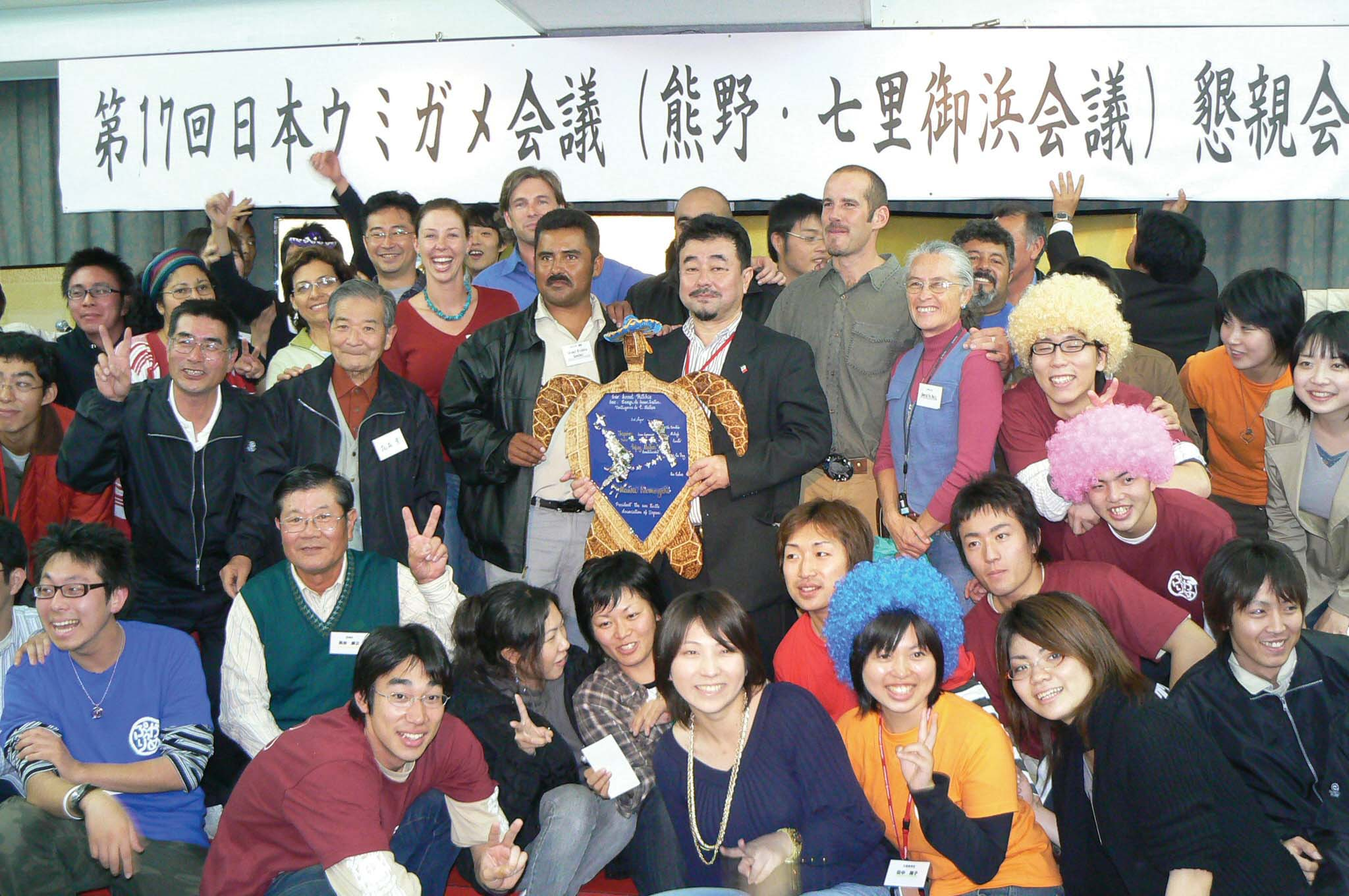 """Sign reads, """"17th Japan Sea Turtle Symposium Social Gathering."""" In Nov. 2006, fishermen, researchers, and resource managers from Mexico, Japan, and the United States gathered to commemorate the 10th anniversary of Adelita's track from Baja California Sur to Japan—the first loggerhead sea turtle to provide physical proof of their trans-Pacific migration via satellite telemetry. The objective of the trip was to share experiences, raise awareness and work toward reducing bycatch of loggerhead sea turtles during a twoweek journey throughout the Japan Archipelago. © PROPENINSULA / I. KINAN"""