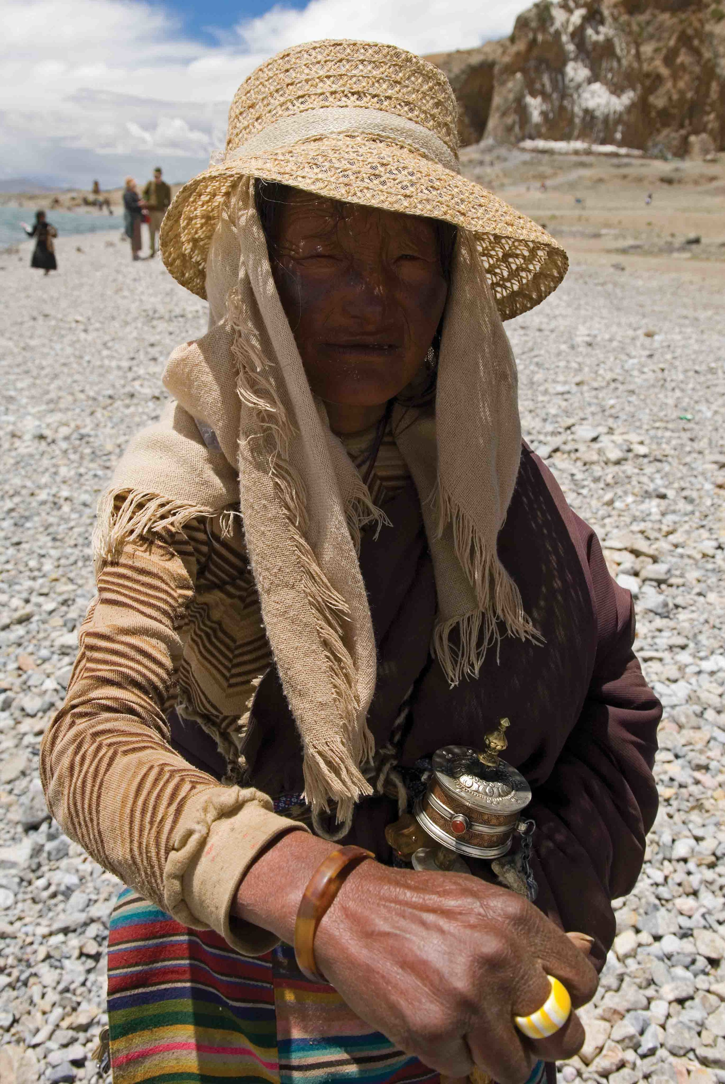 On the shores of Lake Nam Tso on the Tibetan Plateau, at the highest altitude saltwater lake in the world and closer to Mount Everest than to the nearest ocean, a Tibetan woman proudly displays her bekko bracelet. © Roderic B. Mast