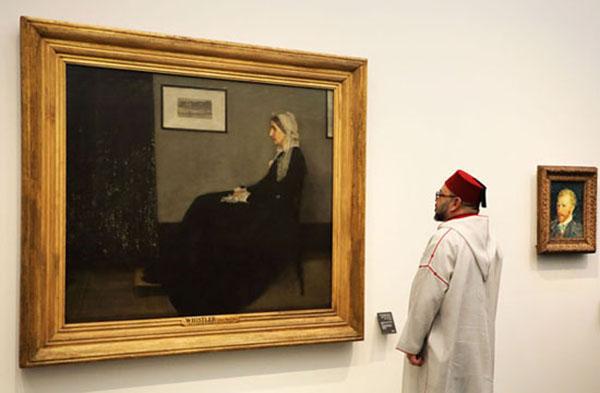 """Fas kralı 6. Muhammed, Louvre Abu Dhabi'de James Abbott McNeill Whistler'ın """"Whistler'ın Annesi"""" adıyla bilinen resmini incelerken. Kral, açılış günü Louvre Abu Dhabi'ye 1 milyar dolar değerinde Fas sanatı eserleri bağışladı.[13]"""