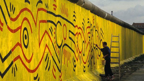 Keith Haring Berlin Duvarı'nı boyuyor