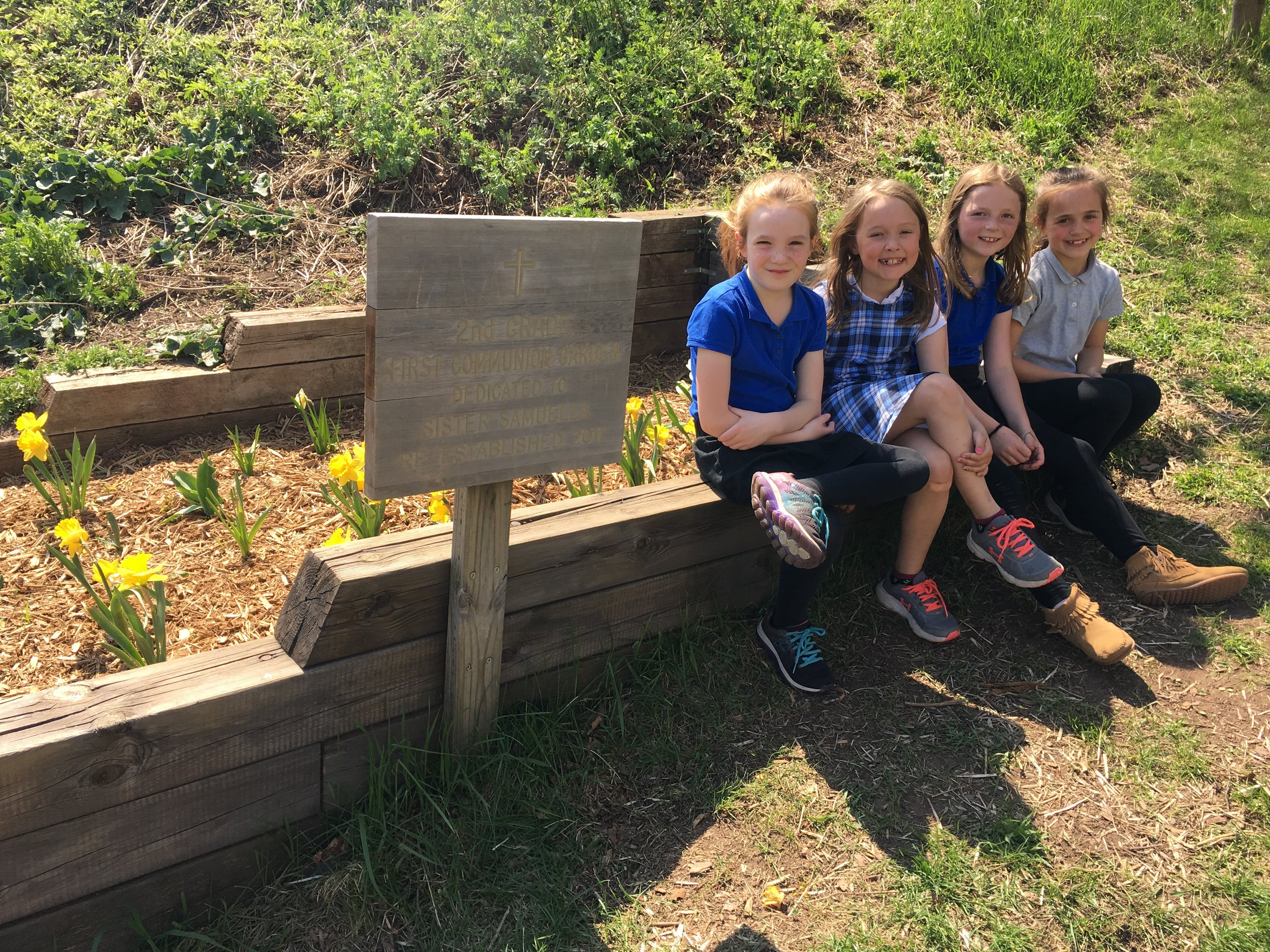 Second grade students pose in front of the First Communion Garden.