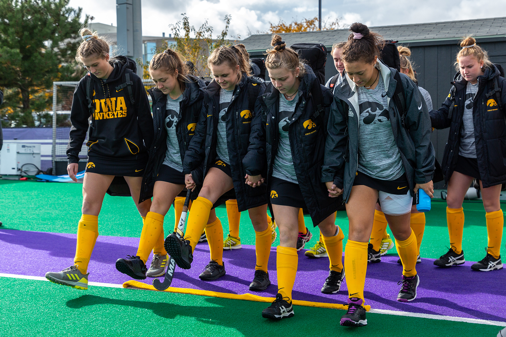 The Iowa Field Hockey Team steps over a golden stripe before the Semifinals in the Big Ten Field Hockey Tournament at Lakeside Field in Evanston, IL on Friday, Nov. 2, 2018. The no. 8 ranked Hawkeyes defeated the no. 7 ranked Wolverines 2-1. The stripe is a piece of Grant Field in Iowa City and is part of a pre-game routine to help the players focus.
