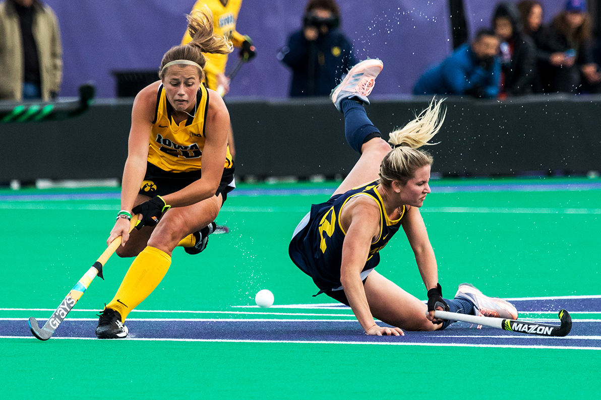 Iowa midfielder Sophie Sunderland tries to control the ball as a Michigan player crashes to the turf during the Semifinals in the Big Ten Field Hockey Tournament at Lakeside Field in Evanston, IL on Friday, Nov. 2, 2018. The no. 8 ranked Hawkeyes defeated the no. 7 ranked Wolverines 2-1.