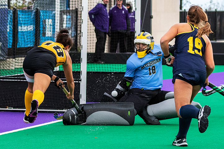 Iowa midfielder Mya Christopher slips a shot over the outstretched leg of Michigan goal keeper Anna Spieker during the Semifinals in the Big Ten Field Hockey Tournament at Lakeside Field in Evanston, IL on Friday, Nov. 2, 2018. The no. 8 ranked Hawkeyes defeated the no. 7 ranked Wolverines 2-1.