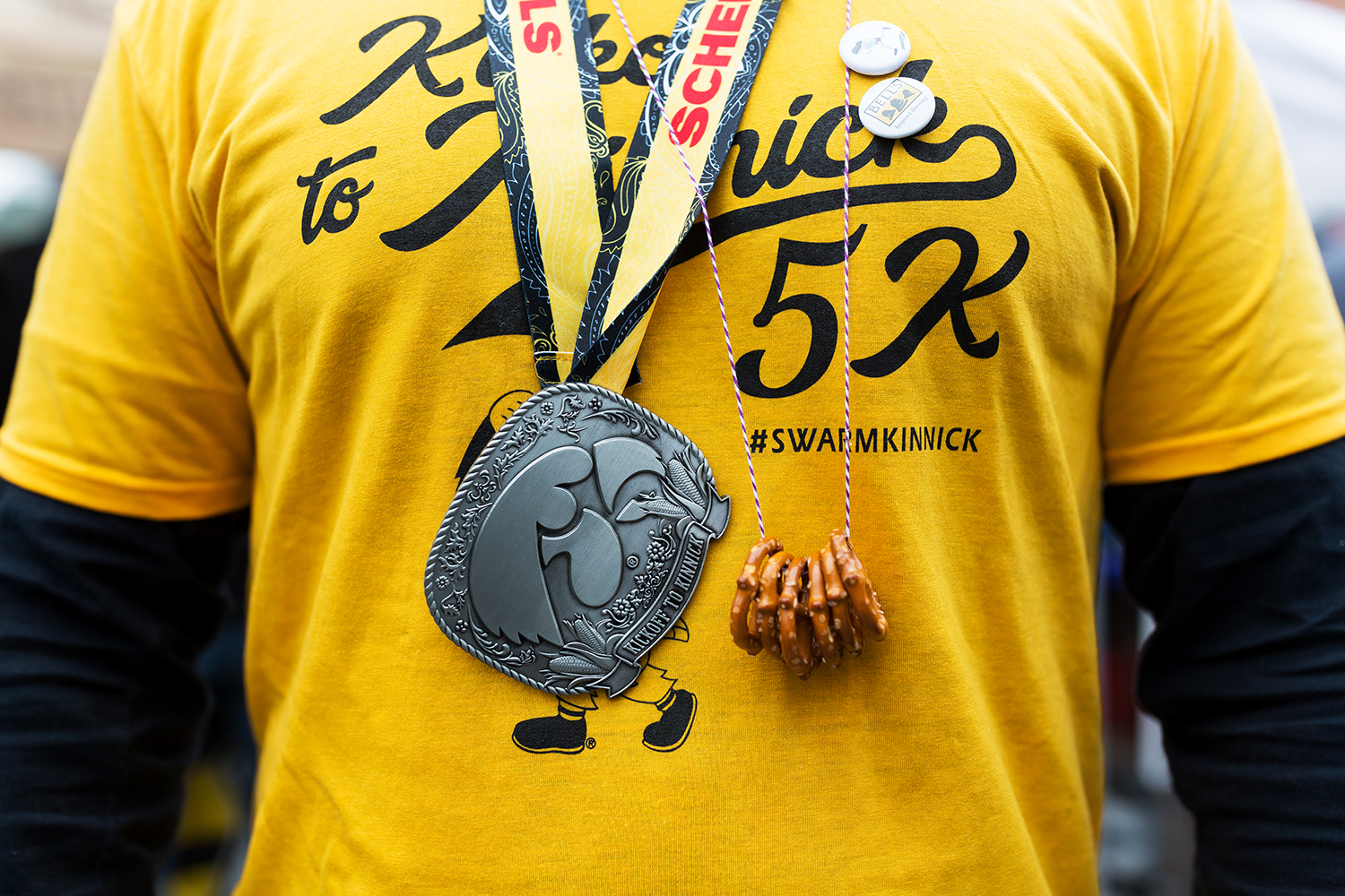A participant in the Kickoff of Kinnick 5k race sports a medal and pretzel necklace at the Northside Oktoberfest in Iowa City on Saturday, Sep. 29, 2018.